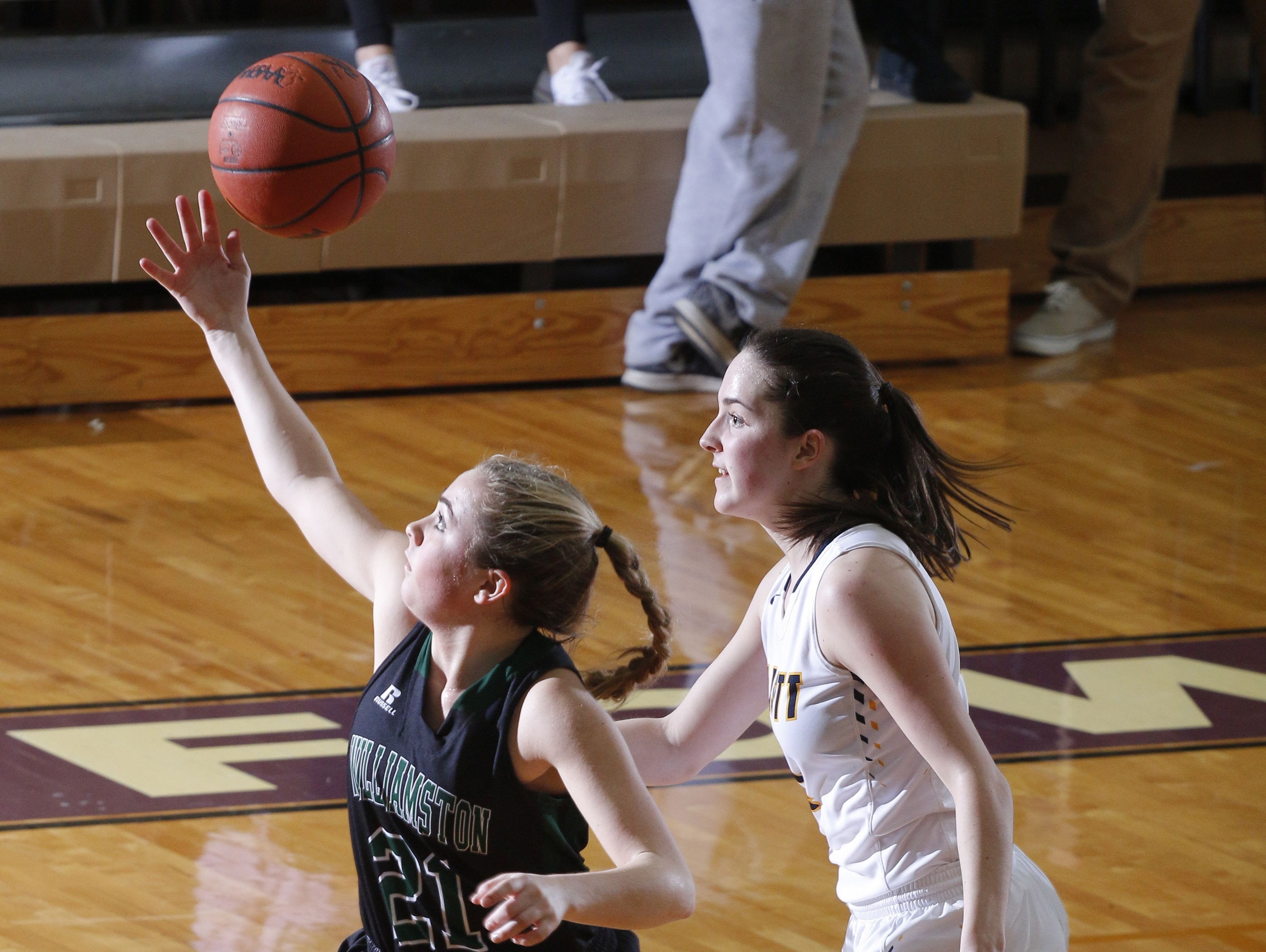 Williamston's Halle Wisbiski, left, reaches for a loose ball against Haslett's Ella McKinney during their district semifinal game Wednesday, March 1, 2017, in Fowlerville, Mich. Williamston won 53-42.