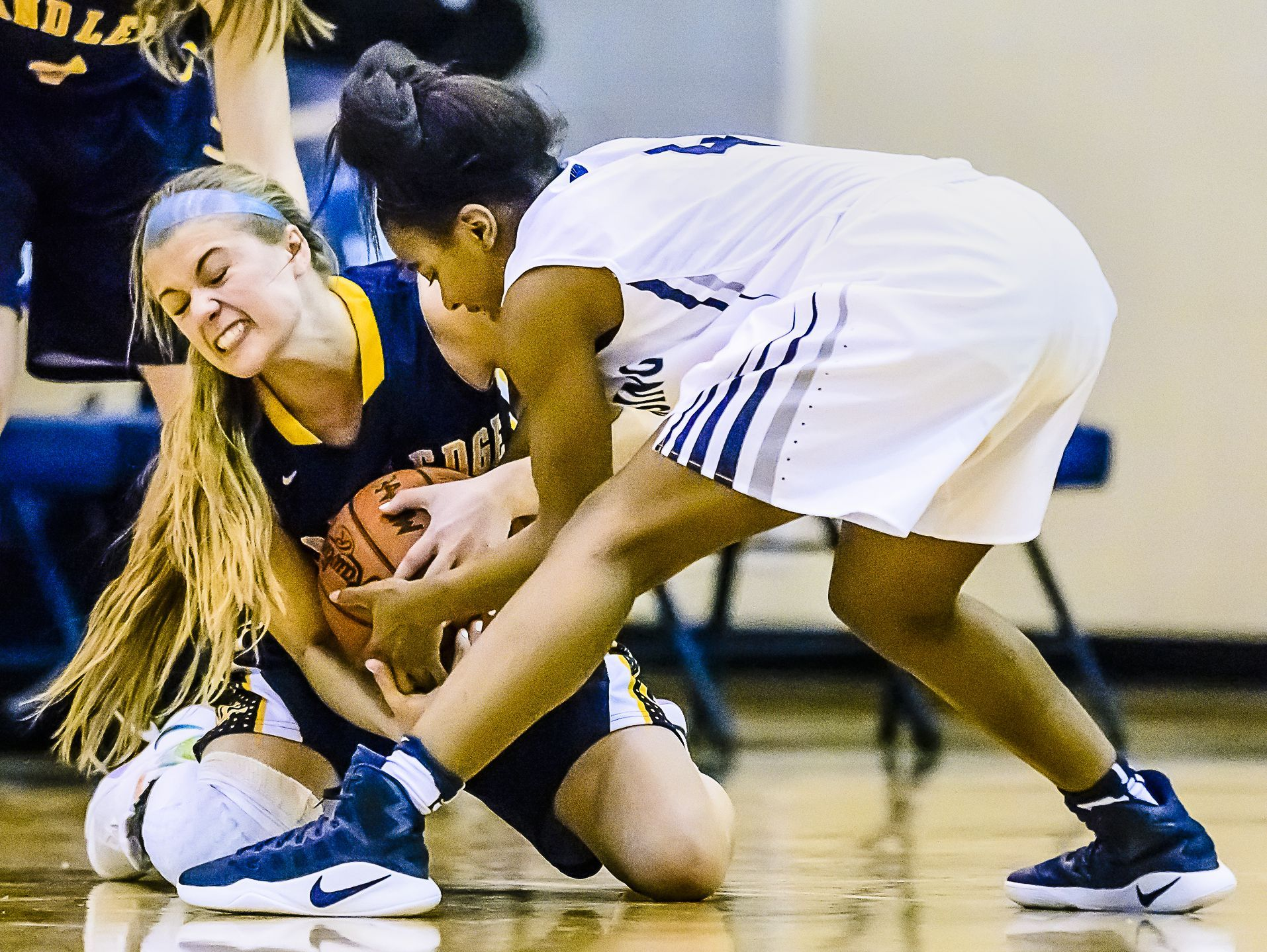 Brooke Rambo ,left, of Grand Ledge and Sanaya Gregory of East Lansing fight for a loose ball during their district semifinal game Wednesday March 1, 2017 at East Lansing High School. KEVIN W. FOWLER PHOTO