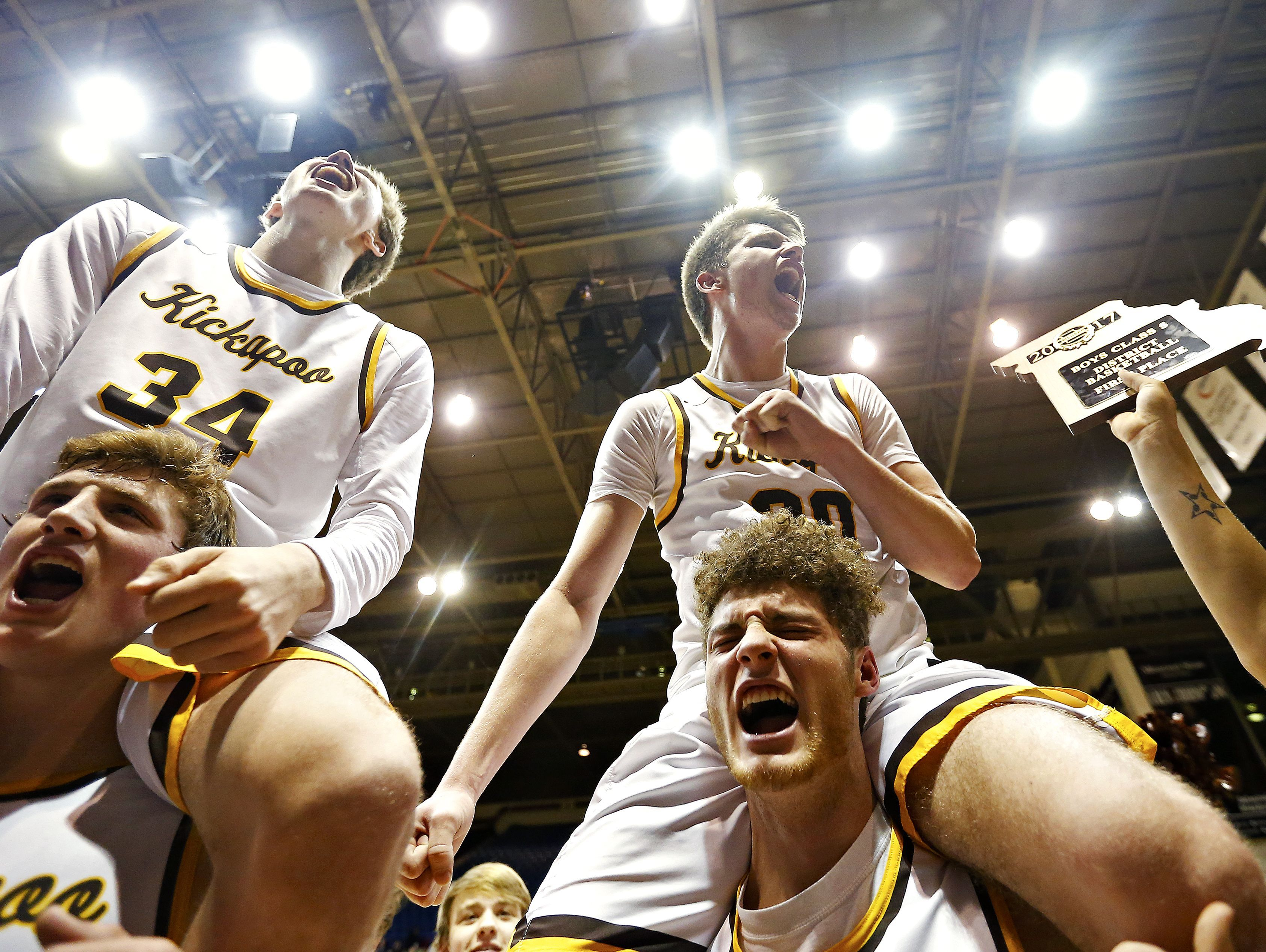 Kickapoo Chiefs players Travis Vokolek (3), Jared Ridder (34), Mitch Closser (44) and Isaac Blakeslee (20) celebrate with their fans after the end of the MSHSAA Class 5 District 11 championship playoff game between the Kickapoo Chiefs and the Ozark Tigers at Hammons Student Center in Springfield, Mo. on March 2, 2017. The Kickapoo Chiefs won the game 52-41.