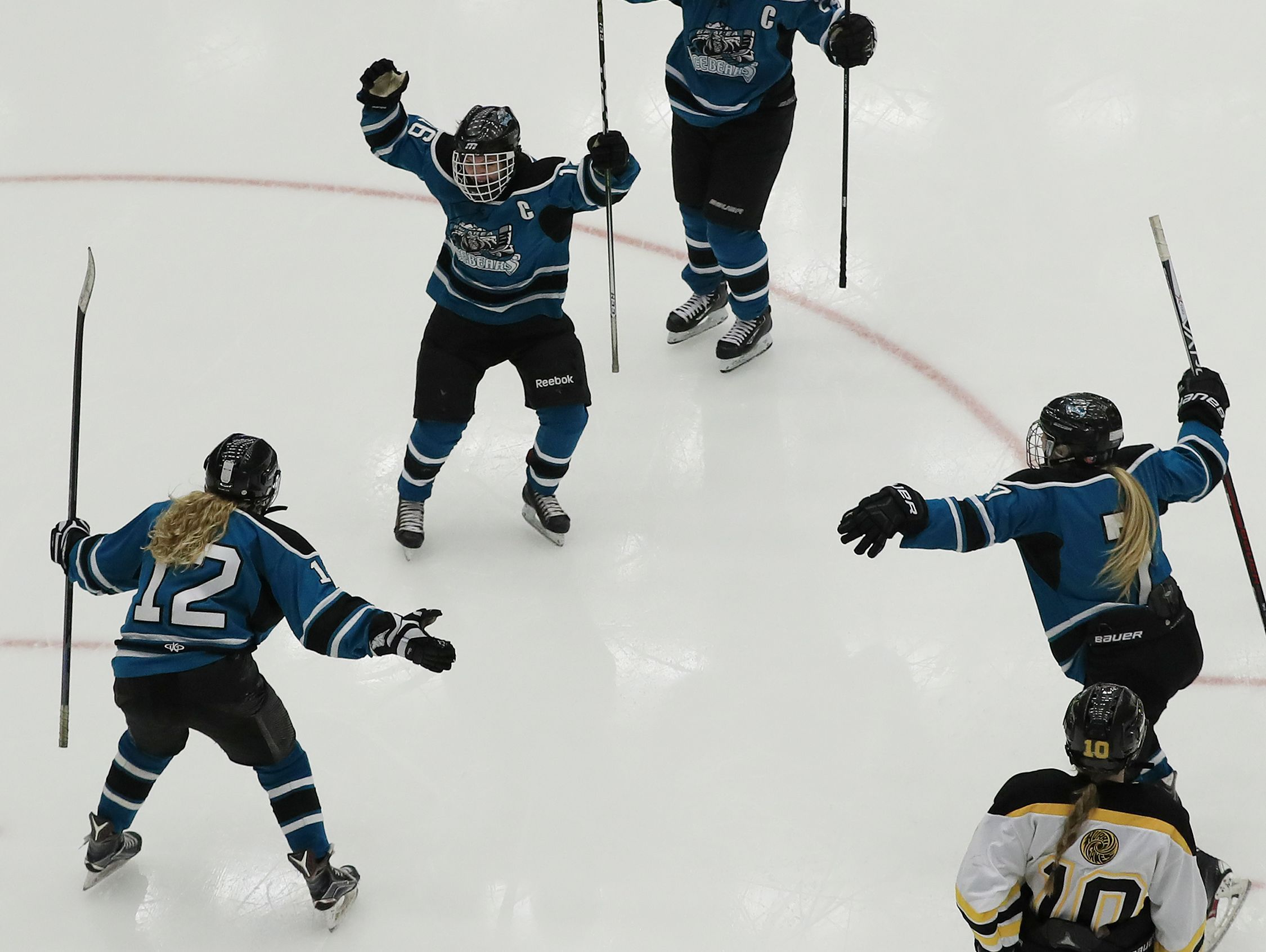 Bay Area Ice Bears forward Abby Anderson (12) celebrates with her teammates after scoring against the Hayward Hurricanes in a WIAA state semifinal girls hockey game Friday at the Alliant Energy Center in Madison.