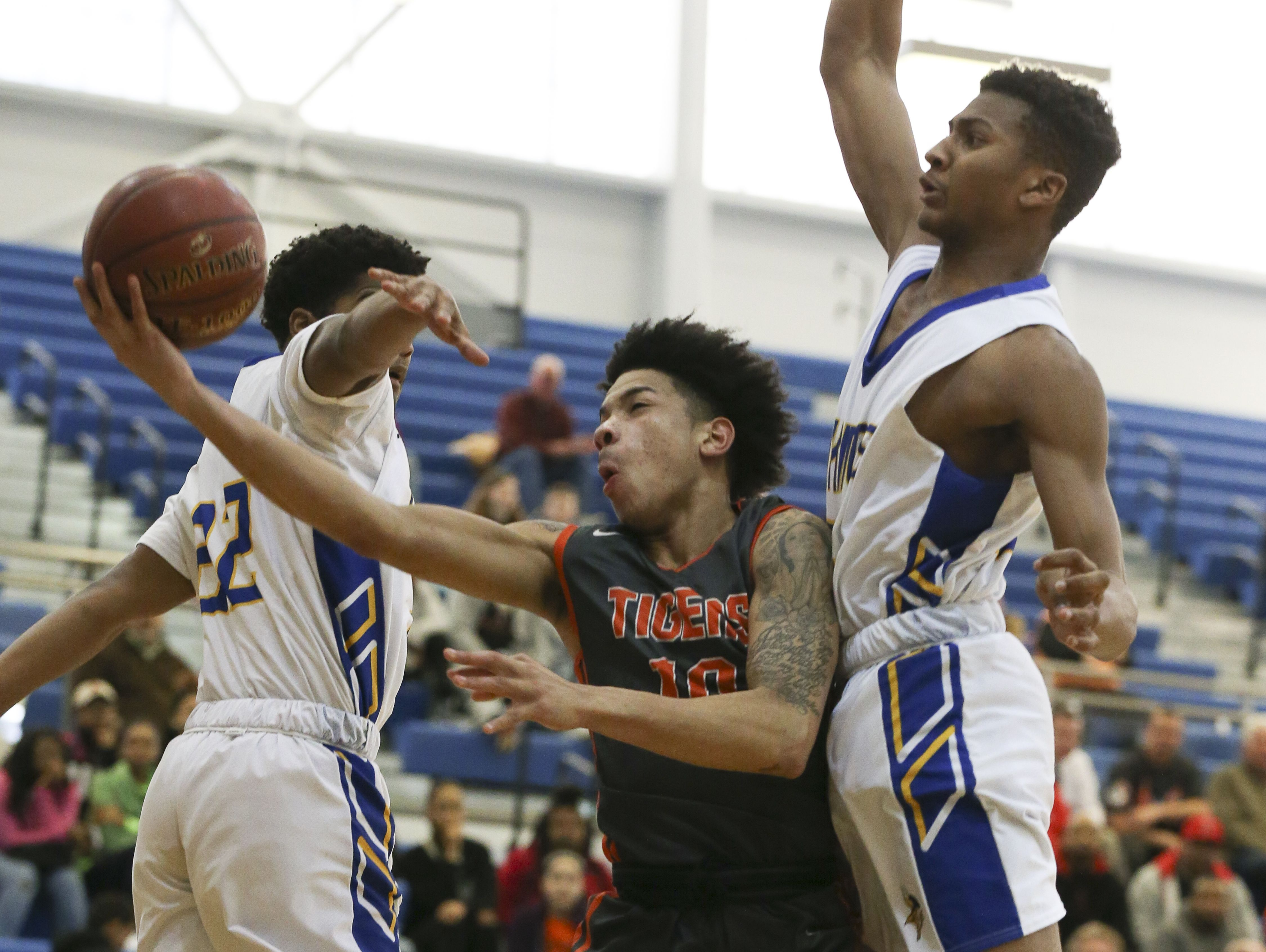 Fern Creek's Ahmad Price (10) splits the defense of Valley's Eric George (22) and Jerry Davis (24) during their 6th Region semifinal game at Valley High School. Mar. 3, 2017