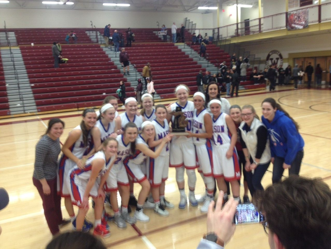The Mason girls basketball team celebrates its 2017 district title after beating Okemos.