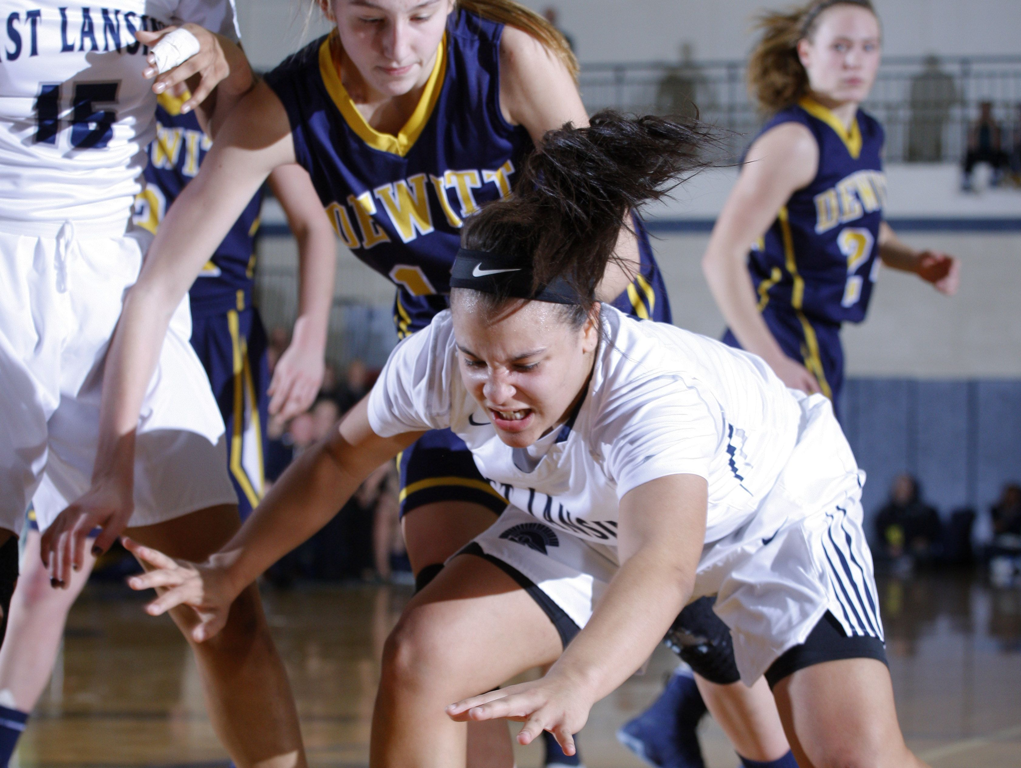 East Lansing's Amelia McNutt, right, and DeWitt's Sydney Mills chase the ball during their district final game Friday, March 3, 2017, in East Lansing, Mich. East Lansing won 48-47.