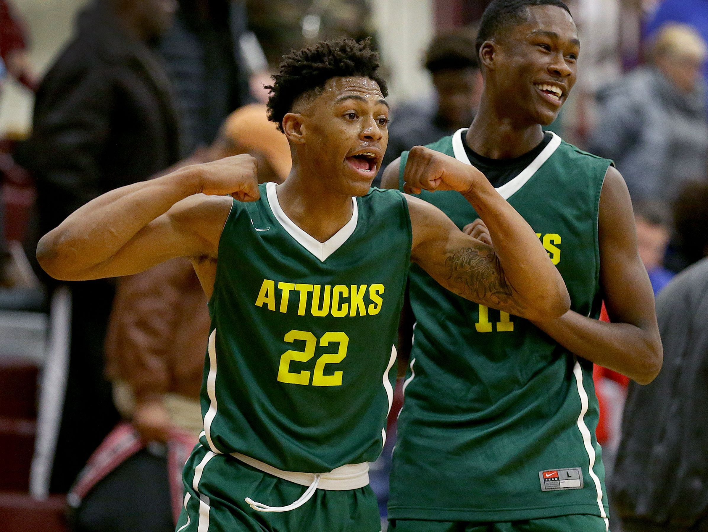 Crispus Attucks Tigers Nike Sibande (22) and Derrick Briscoe (11) begin to celebrate their win in their IHSAA 3A Sectional basketball game Friday, March 3, 2017, evening at Brebeuf Jesuit Preparatory School. The Crispus Attucks Tigers defeated the Manual Redskins 65-53.