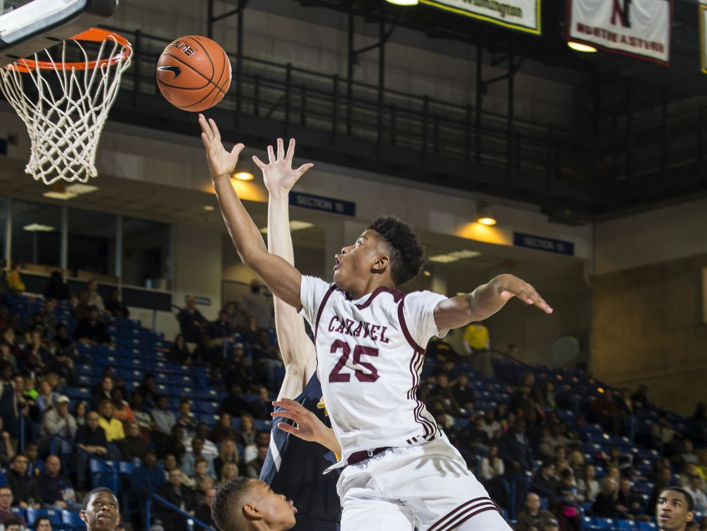 Caravel's Dwayne Earl puts up a shot over Sanford's Corey Perkins in the second half of Caravel Academy's 66-56 win over Sanford School in the quarterfinals of the DIAA Boy's Basketball Tournament at the Bob Carpenter Center in Newark on Sunday afternoon.