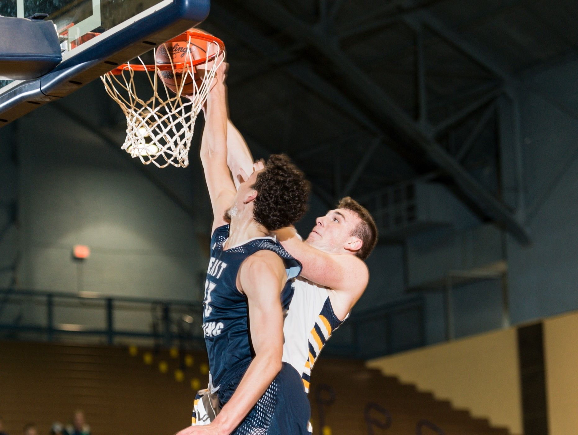 Brandon Johns ,foreground, of East Lansing blocks a lay up attempt by Nick Crocker of Grand Ledge during their district quarterfinal game Monday March 6, 2017 at Don Johnson Fieldhouse in Lansing.