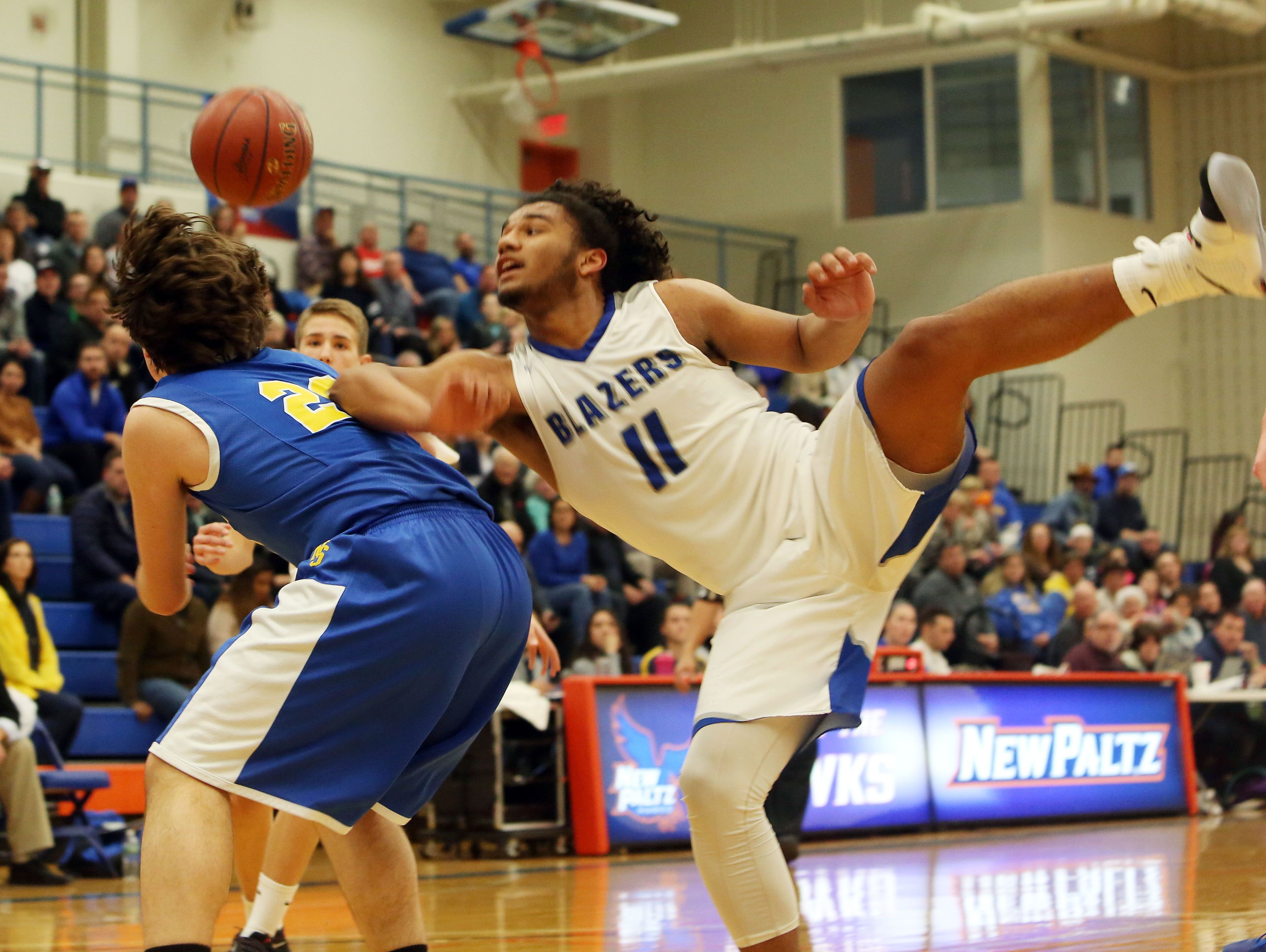 Millbrook High School's Drew Jackson, center, battles for a rebound with North Salem's Miles D'Alessandro during a Class C state regional semifinal at SUNY New Paltz on Tuesday.