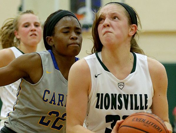 Zionsville Eagles Rachel McLimore (32) drives to the basket around Carmel Greyhounds Tomi Taiwo (22) in the first half of their game Tuesday, November 15, 2016, evening at Zionsville High School.