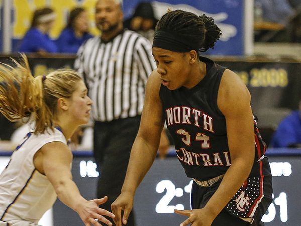 North Central Panthers' Ajanae´ Thomas (34) slips past Carmel Greyhounds' Olivia Christy (2) at Carmel High School on Friday, Dec. 16, 2016. Harris was made the layup and was fouled on the play.