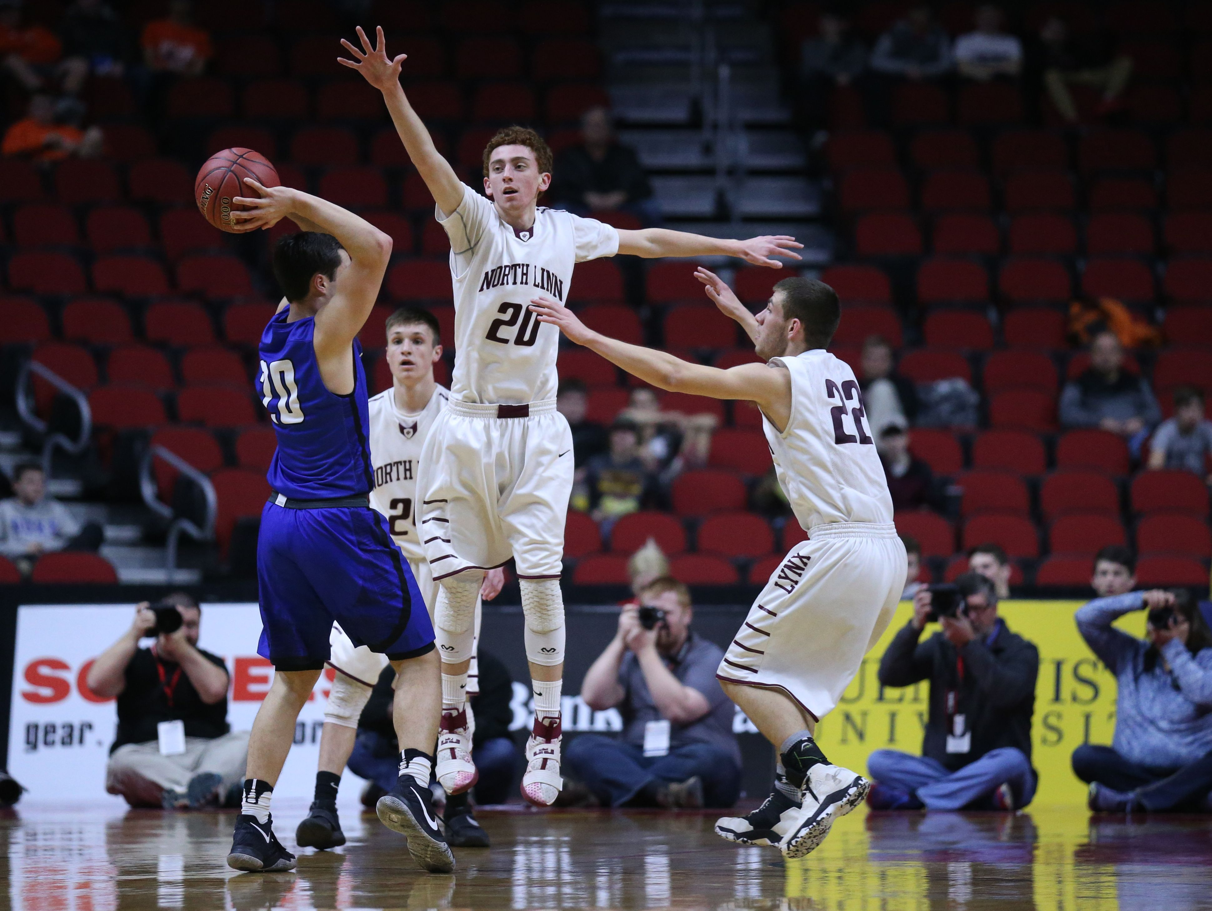 Gladbrook-Reinbeck's Joe Smoldt passes the ball past two North Linn defenders during the state boy's basketball 1A semifinal between North Linn and Gladbrook-Reinbeck on Thursday, March 9, 2017, in Wells Fargo Arena.