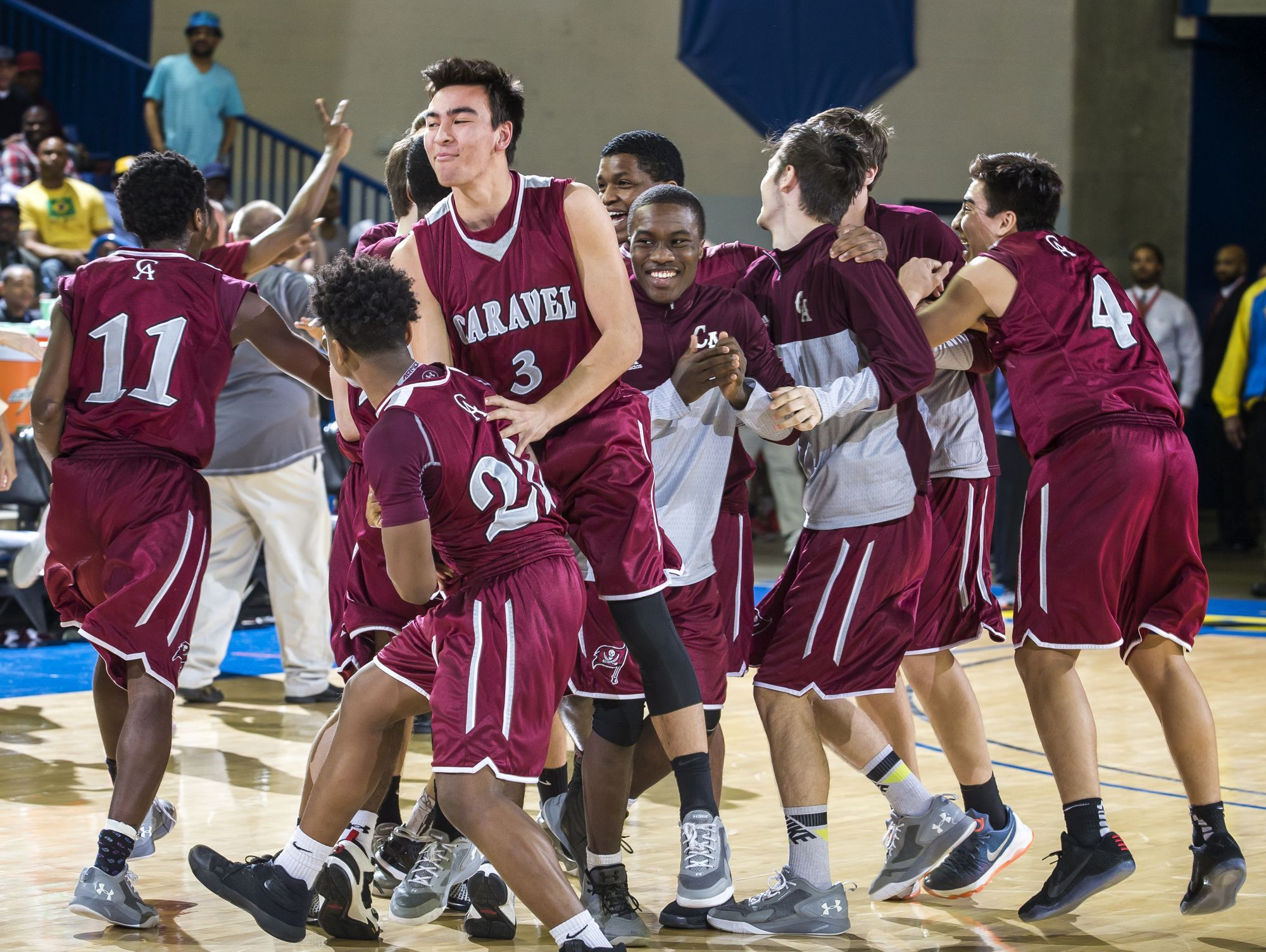 Caravel players celebrate following their 48-47 win over St. Thomas More Academy in the DIAA Boy's State Basketball Tournament semi-finals at the Bob Carpenter Center in Newark on Thursday evening.
