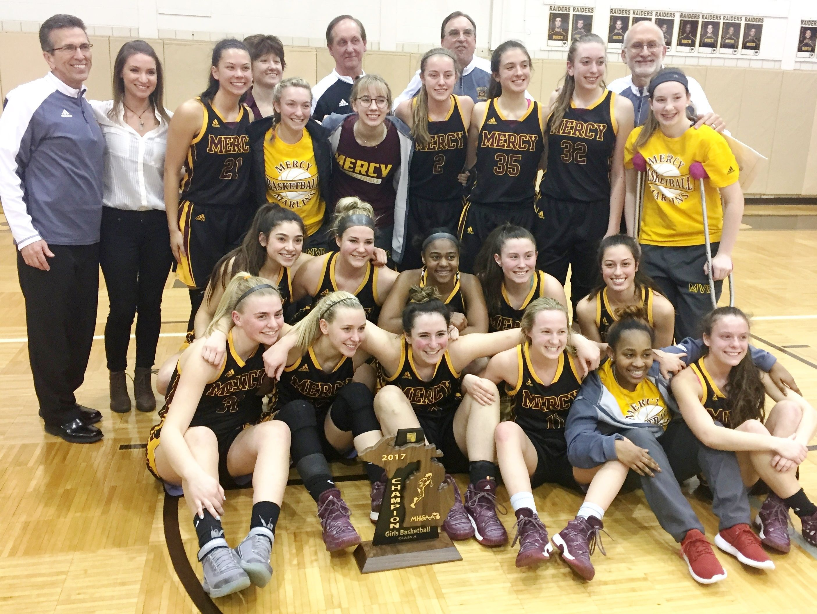 The Mercy girls basketball team celebrates after winning the Class A regional at North Farmington.