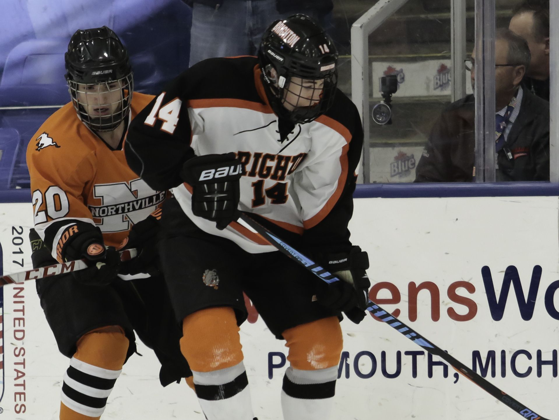 Brighton's Spencer Gehres (14) battles for the puck with Northville's Danny Scorzo during the Bulldogs' 5-0 state semifinal victory Friday.