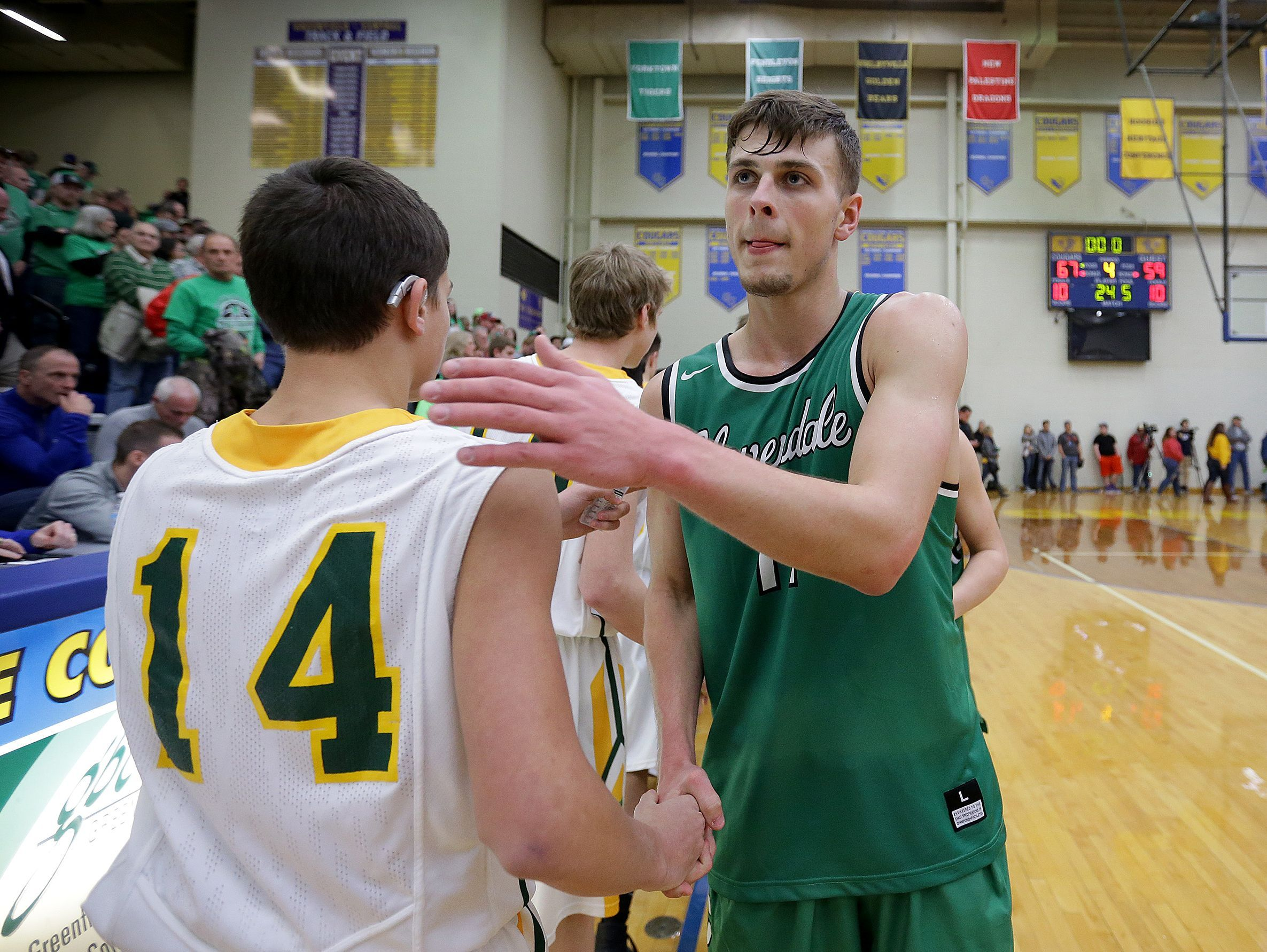 Cooper Neese (11) congratulates the Northeastern players at the end of their IHSAA Boys Regional basketball game, Saturday at Greenfield-Central High School. Cloverdale lost to Northeastern, 67-59.