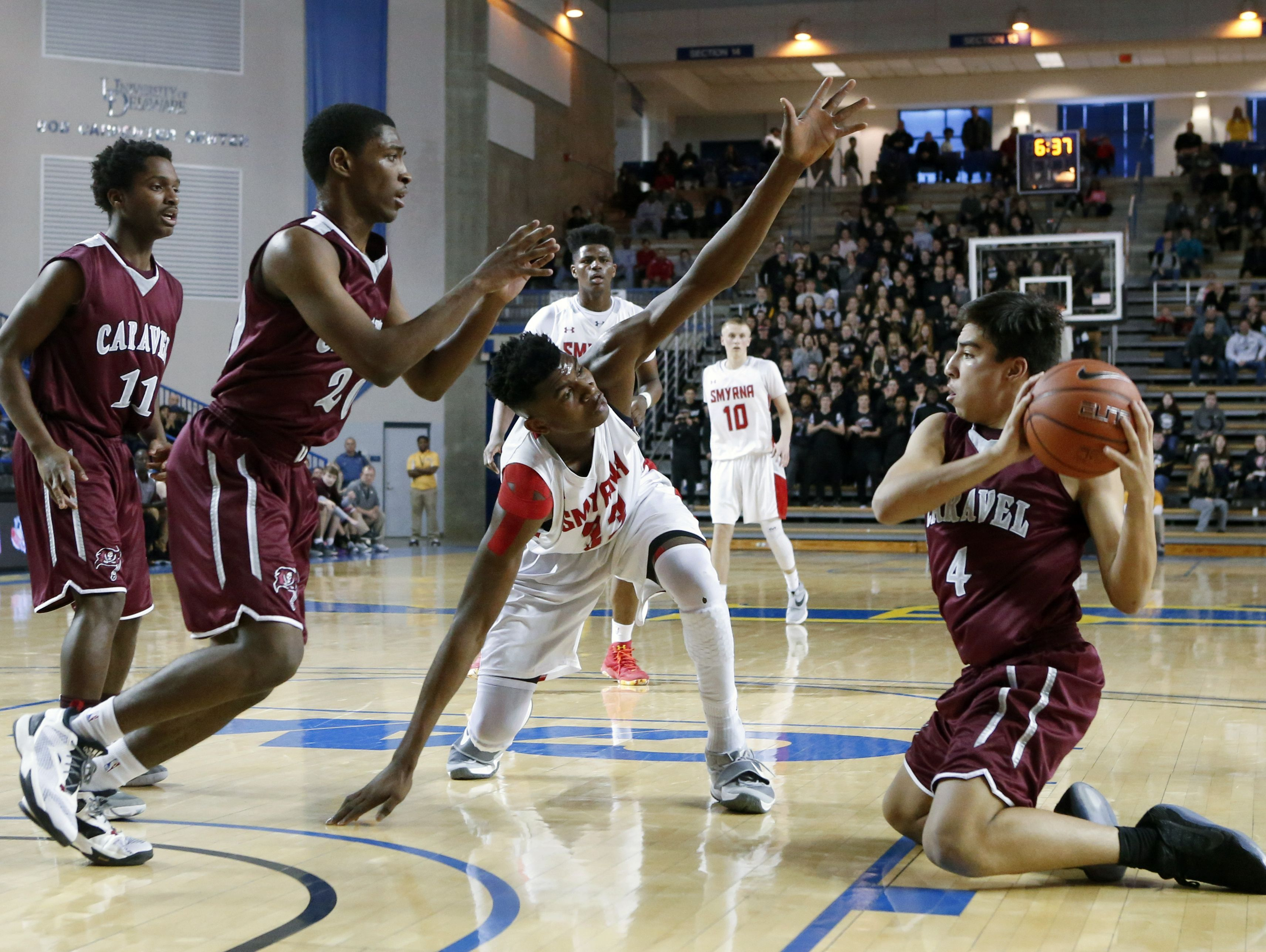 Caravel's Brandon Sengphachanh snags a loose ball in front of Smyrna's Zubi Nwankwo and teammates Mandela Montgomery (left) and Trevon Alderman in the second half of the Eagles' 61-53 win in the DIAA state tournament title game at the Bob Carpenter Center Saturday.