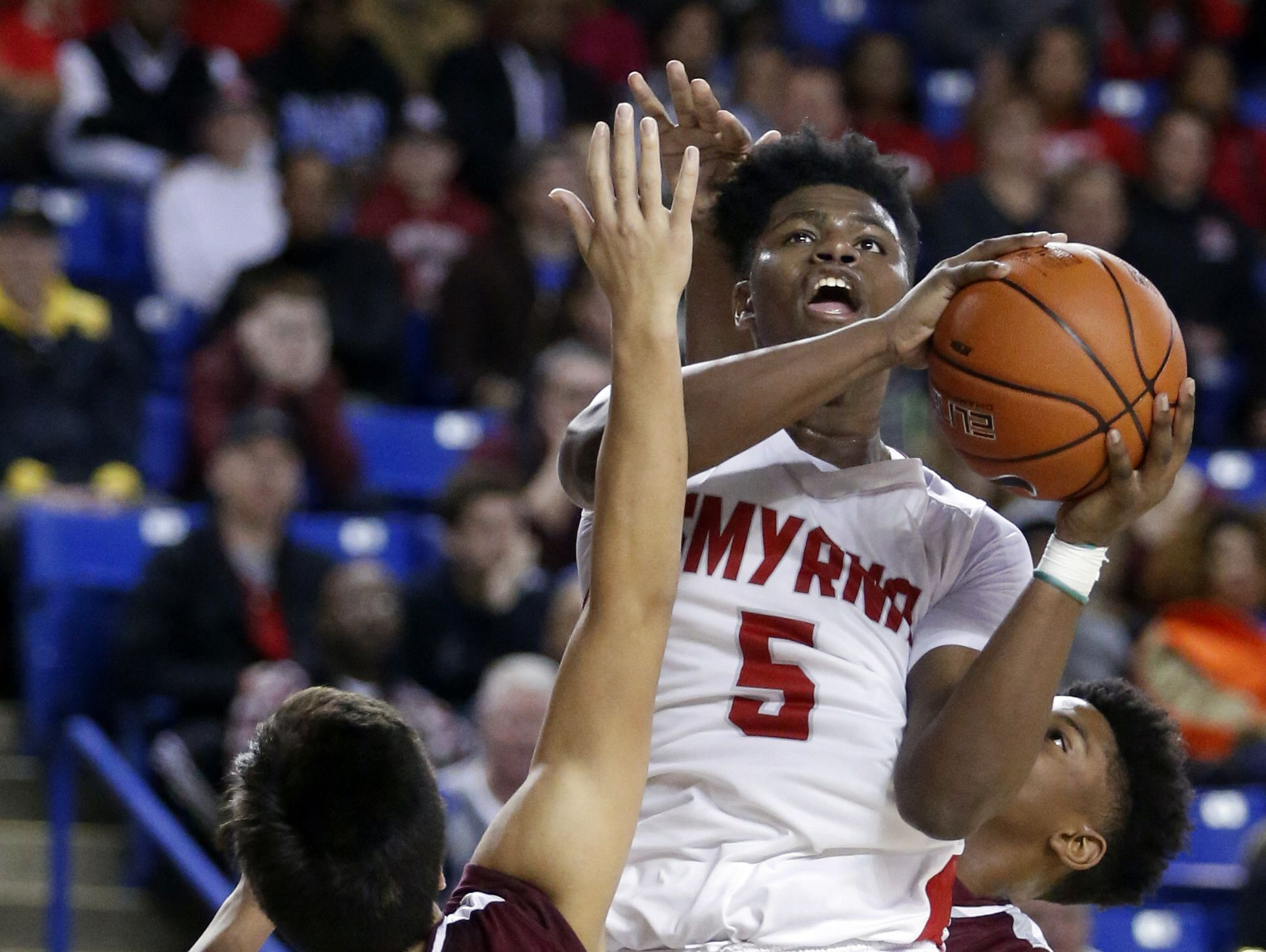 Smyrna's Jaymeir Garnett shoots over Caravel's Brandon Sengphachanh in the second half of the Eagles' 61-53 win in the DIAA state tournament title game at the Bob Carpenter Center Saturday.