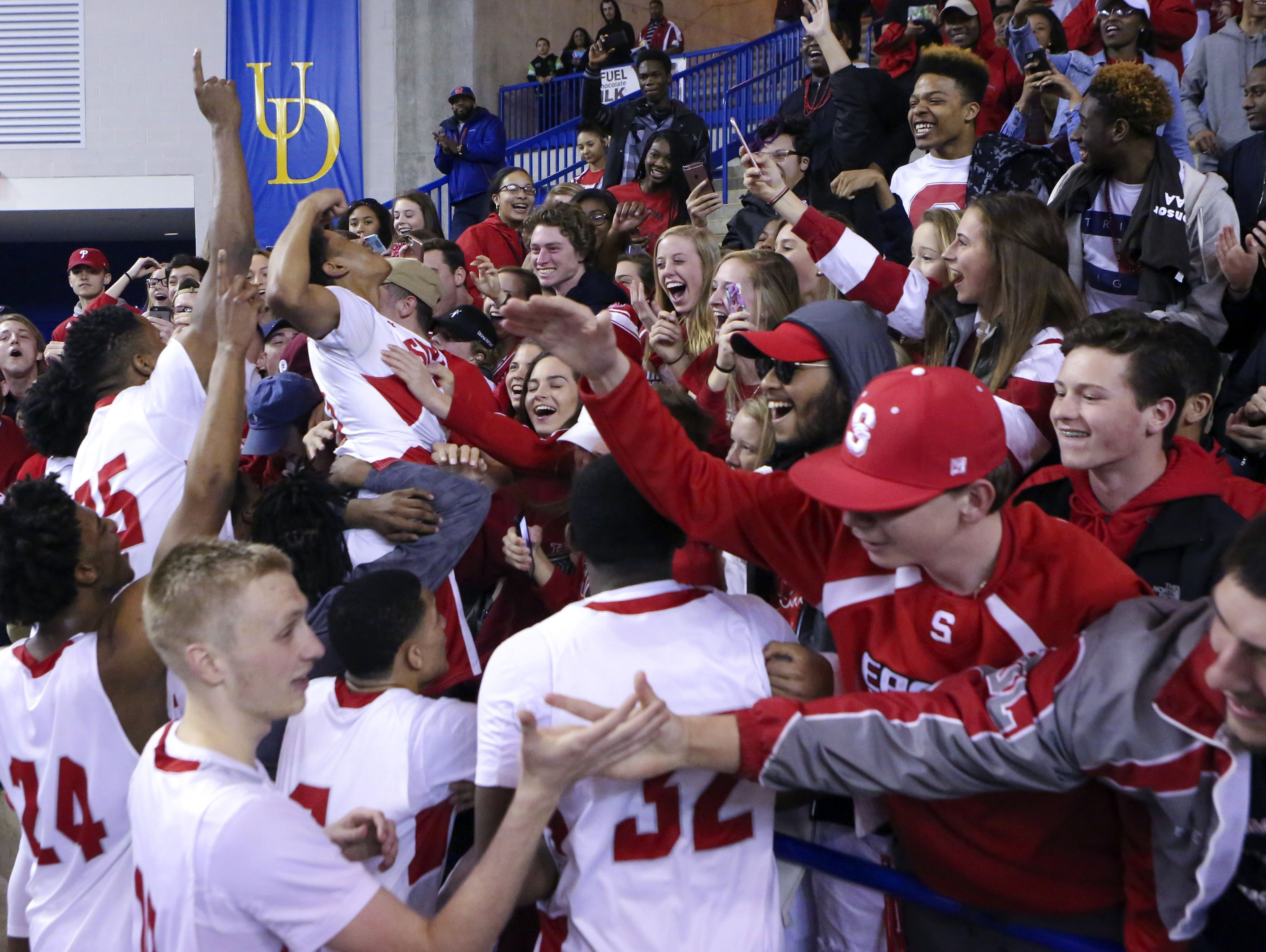 Smyrna team members celebrate with their classmates after beating Caravel 61-53 to win the DIAA state tournament title game at the Bob Carpenter Center Saturday.