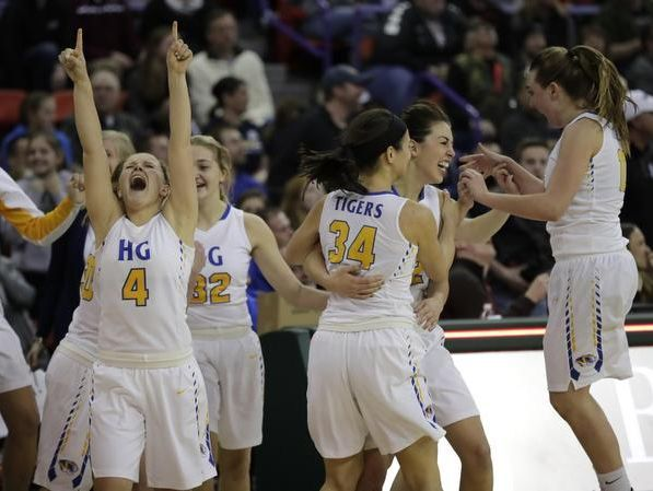 Howards Grove players celebrate a dramatic 44-43 victory against Aquinas for the WIAA Division 4 girls basketball championship game on Saturday at the Resch Center.