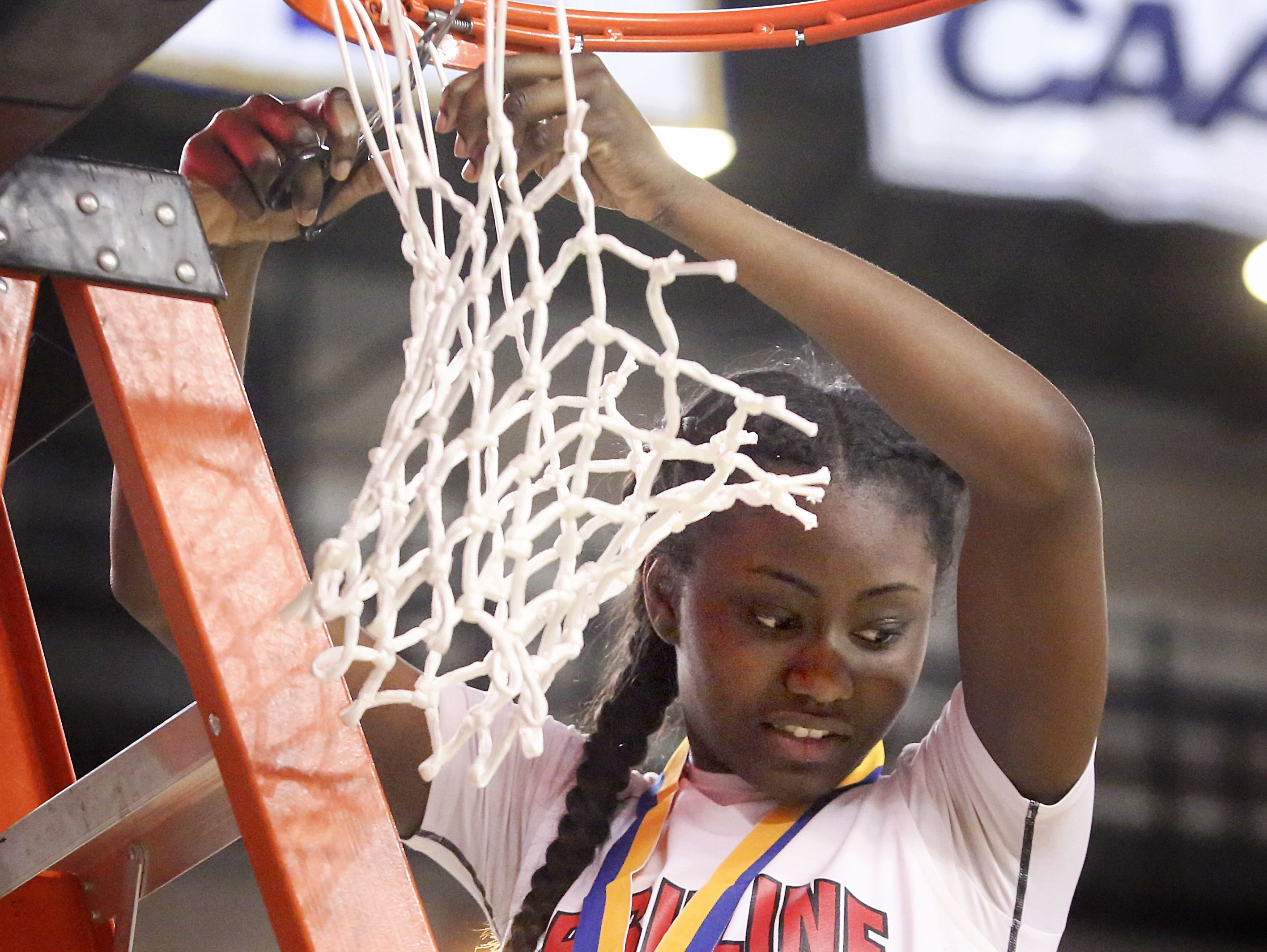 Ursuline's Kryshell Gordy claims her share of the net after the Raiders' 54-32 win in the DIAA Girls Basketball Tournament title game at the Bob Carpenter Center last Friday.