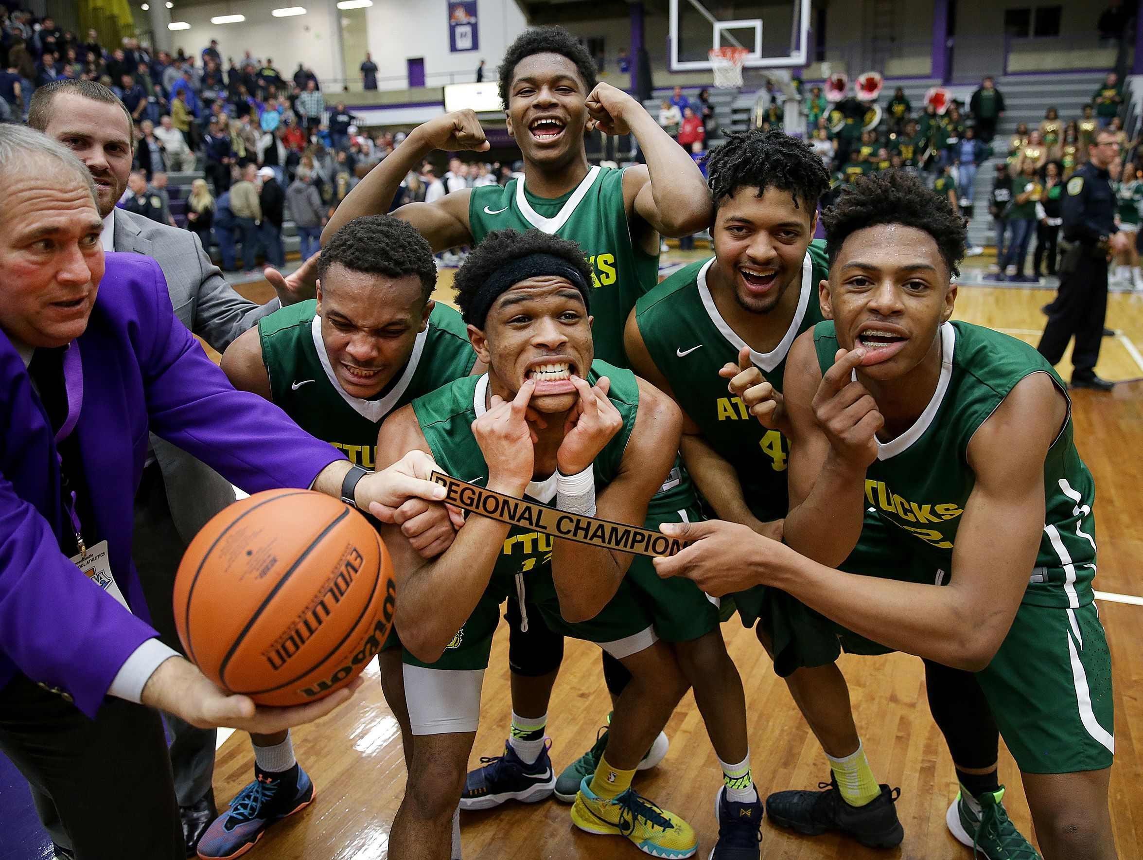Crispus Attucks Tigers celebrate their win in the IHSAA Boys Regional championship game Saturday at the McAnally Center in Greencastle.