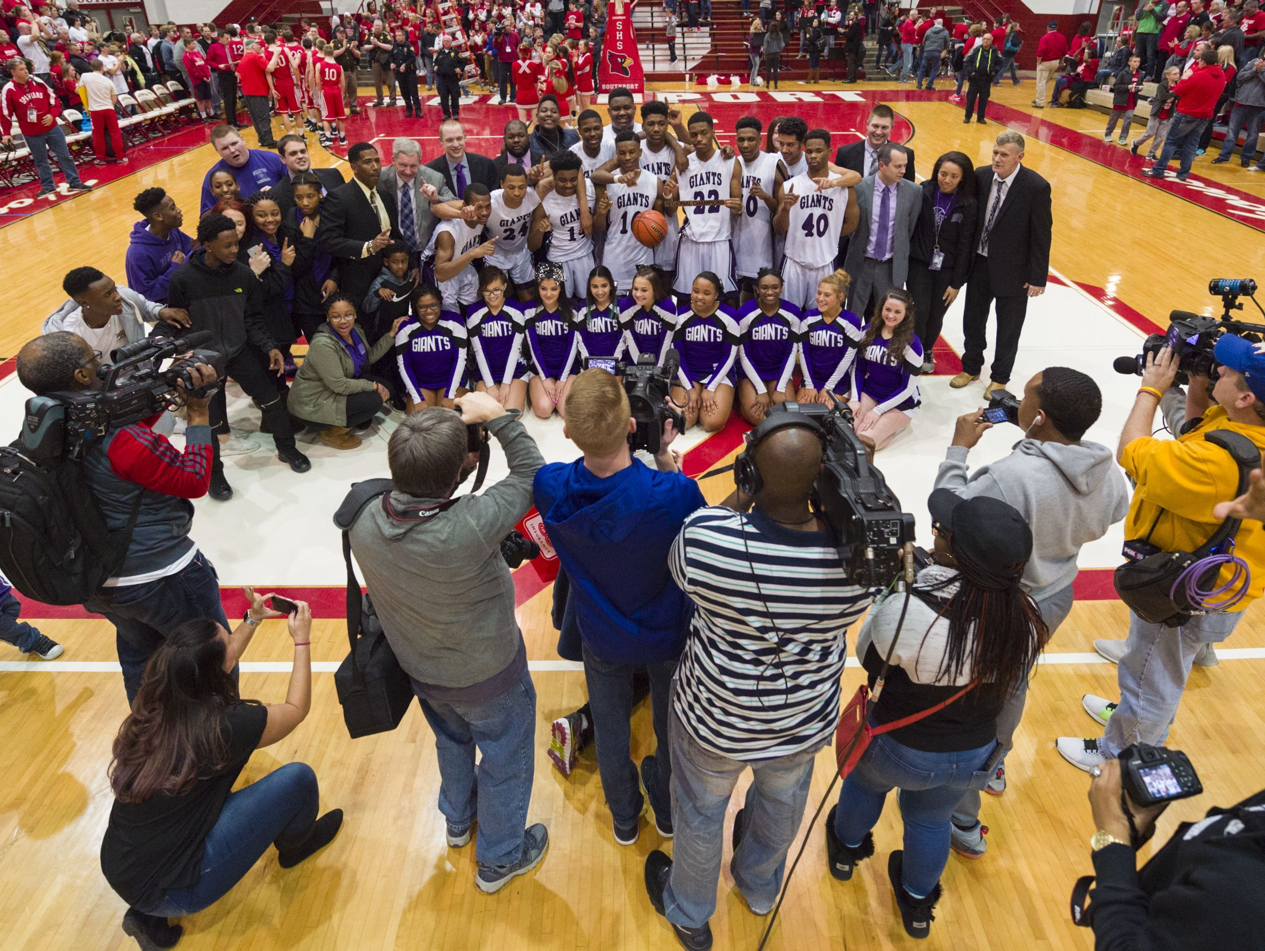 Ben Davis players and staff pose for photographers after winning an IHSAA Boys Basketball Regional championship game, Saturday at Southport High School.