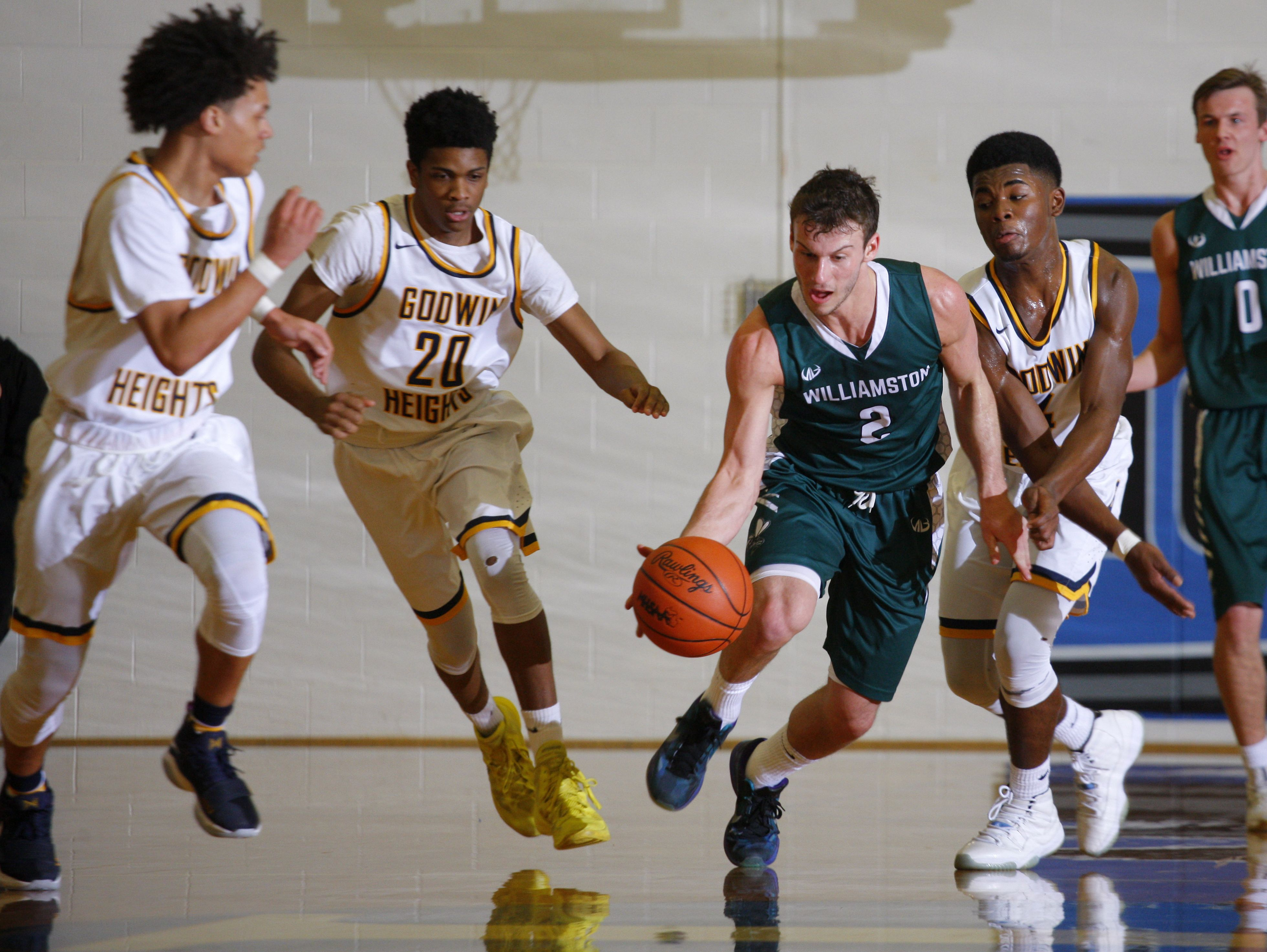 Williamston's Sy Barnnett (2) maneuvers through a host of Godwin Heights defenders during their MHSAA regional game Monday, March 13, 2017, in Ionia, Mich. Williamston won 69-65..
