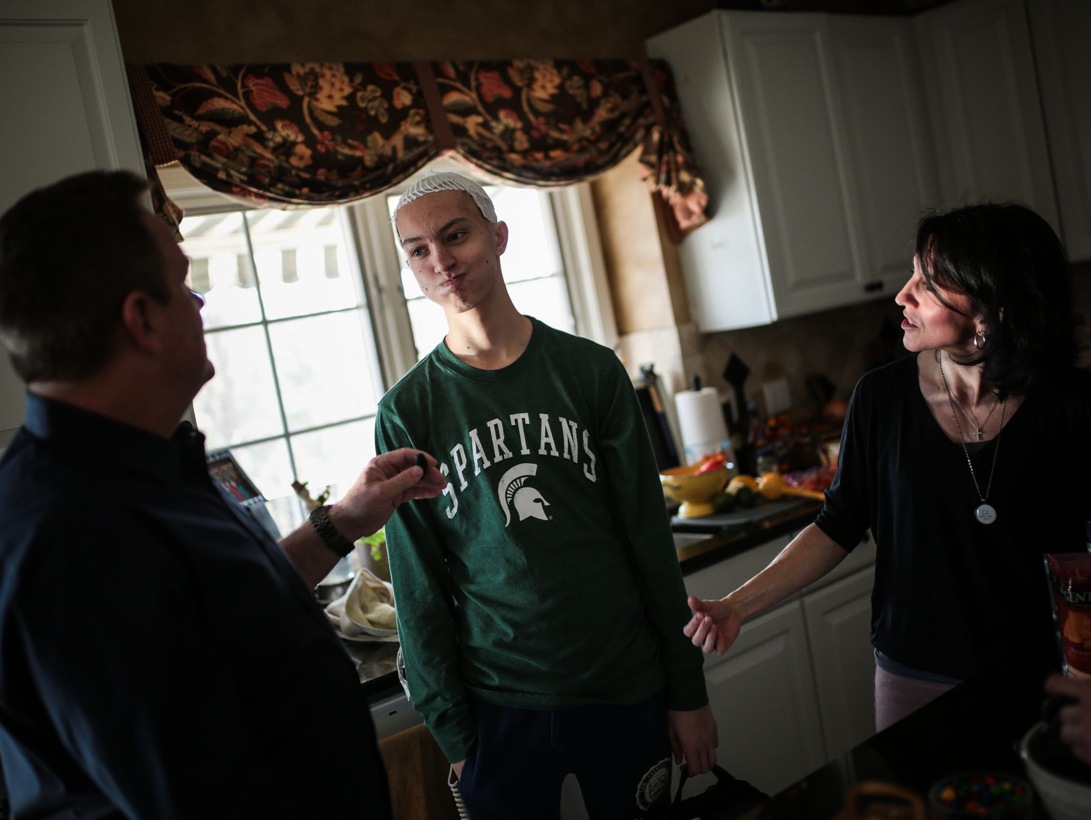 Sam Kell, 16, of Rochester, center, listens to his stepdad Michael Spehn, 53, of Rochester, and his mother Gina Kell Spehn, 47, of Rochester, at their home on Saturday, March 11, 2017.