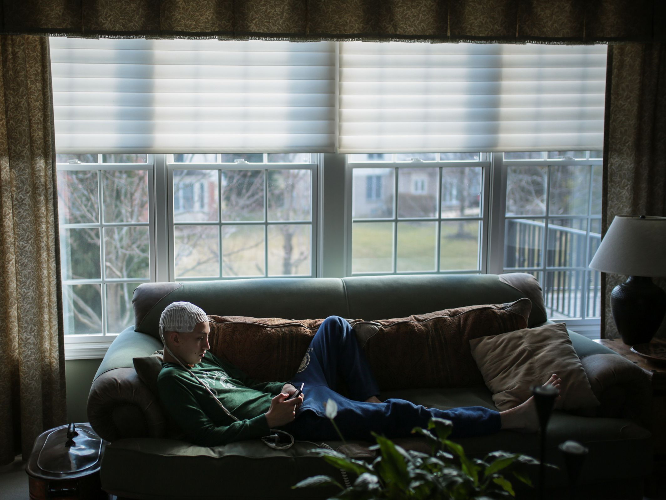 Sam Kell, 16, of Rochester, rests on a coach in the living room of his home on Saturday March 11, 2017 in Rochester.