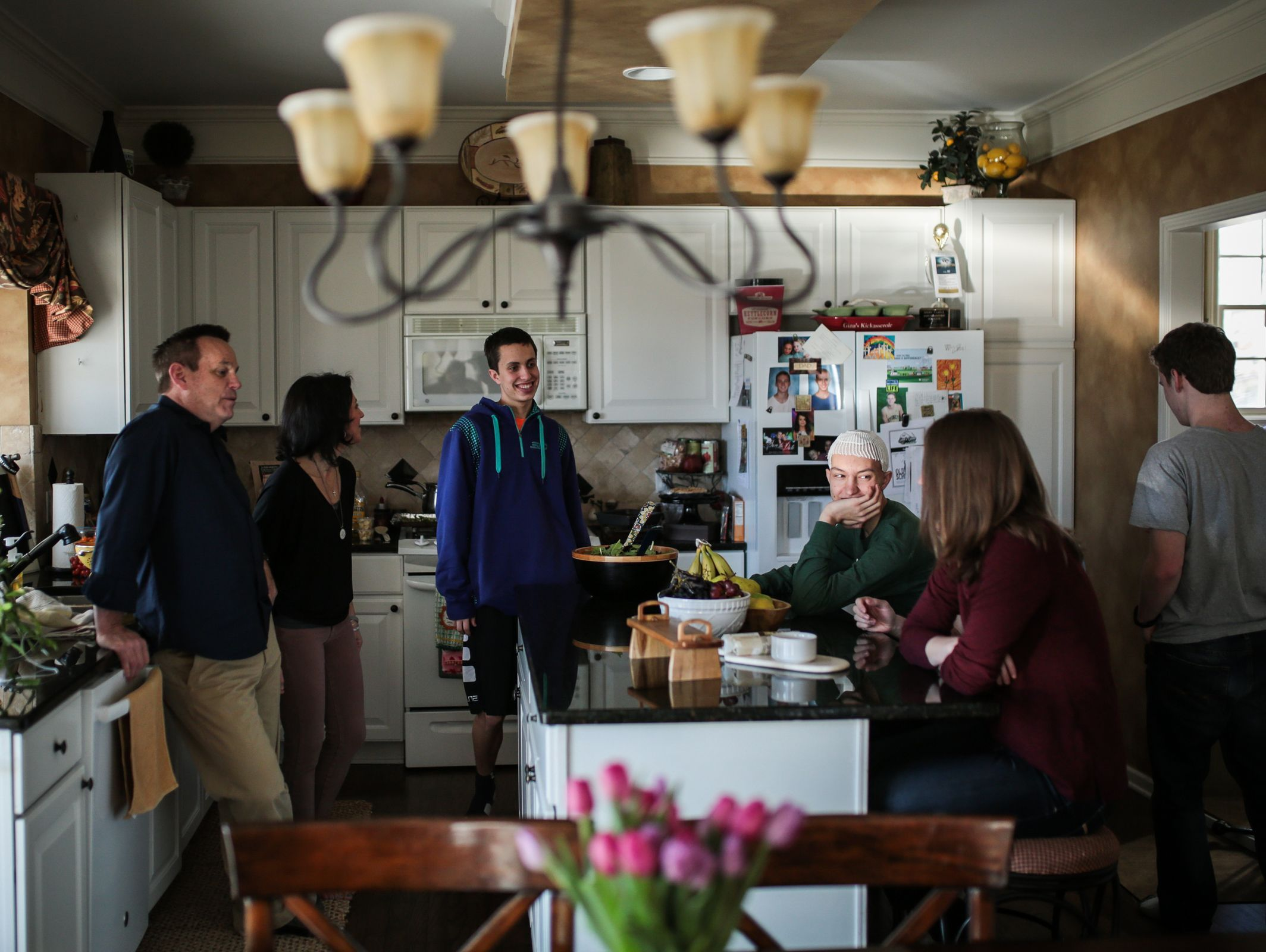 The Kell-Spehn family and friends are seen talking in the kitchen before preparing for a birthday party at their home on Saturday March 11, 2017 in Rochester, MI.