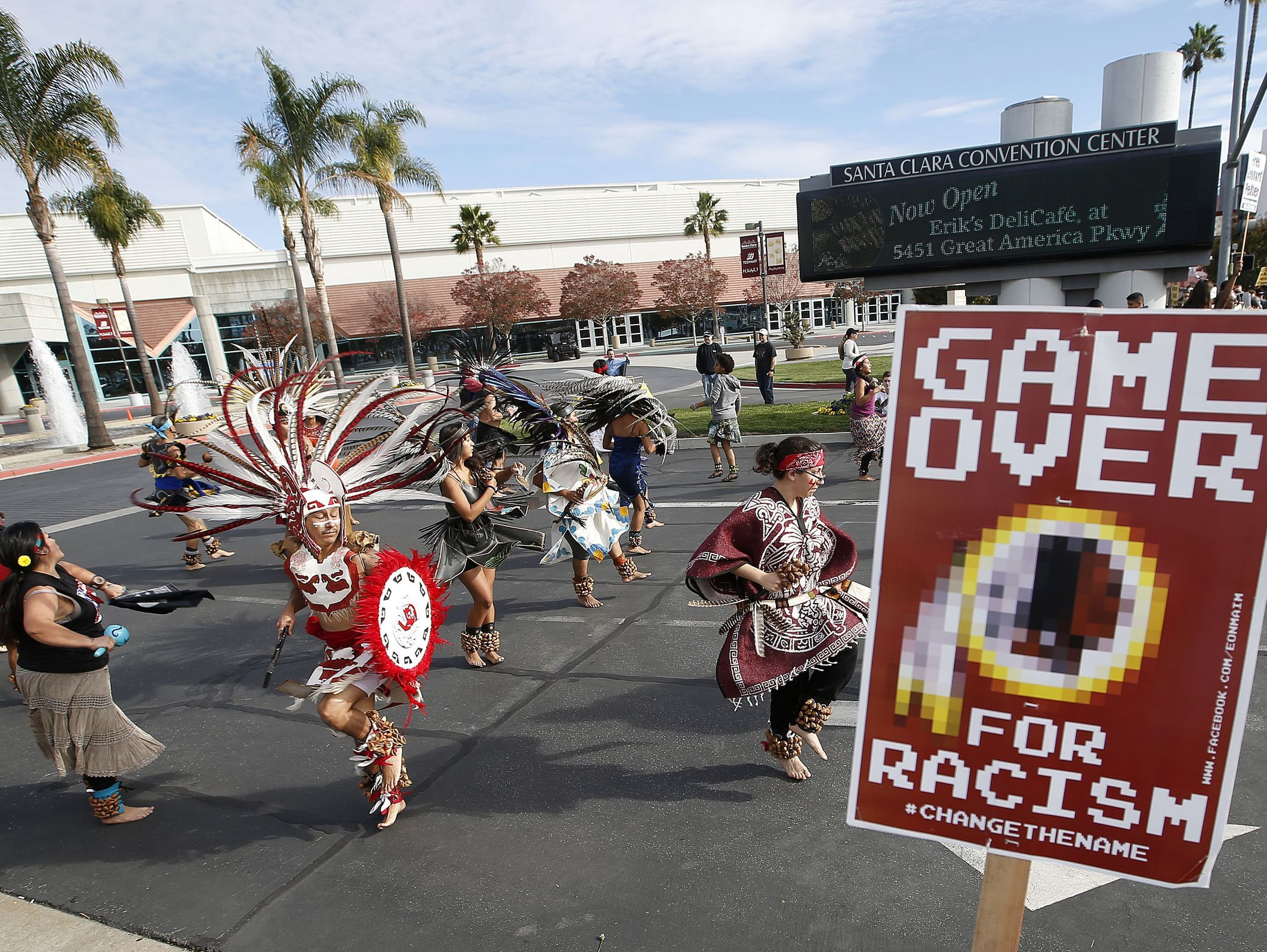 In this 2014 file photo, a group in California protests the Washington Redskins' name before an NFL football game. The same issue is found in Paw Paw, Mich., where the state is considering withholding funding until it changes its Redskins mascot.