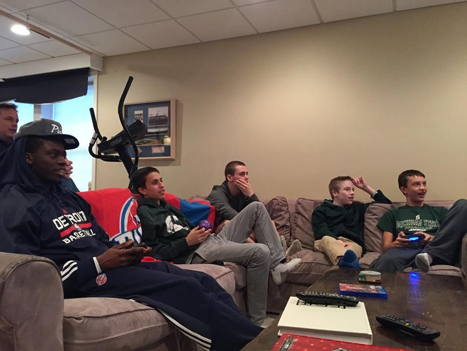 Pistons guard Reggie Jackson plays an NBA video game with Sam Kell in Sam's basement.
