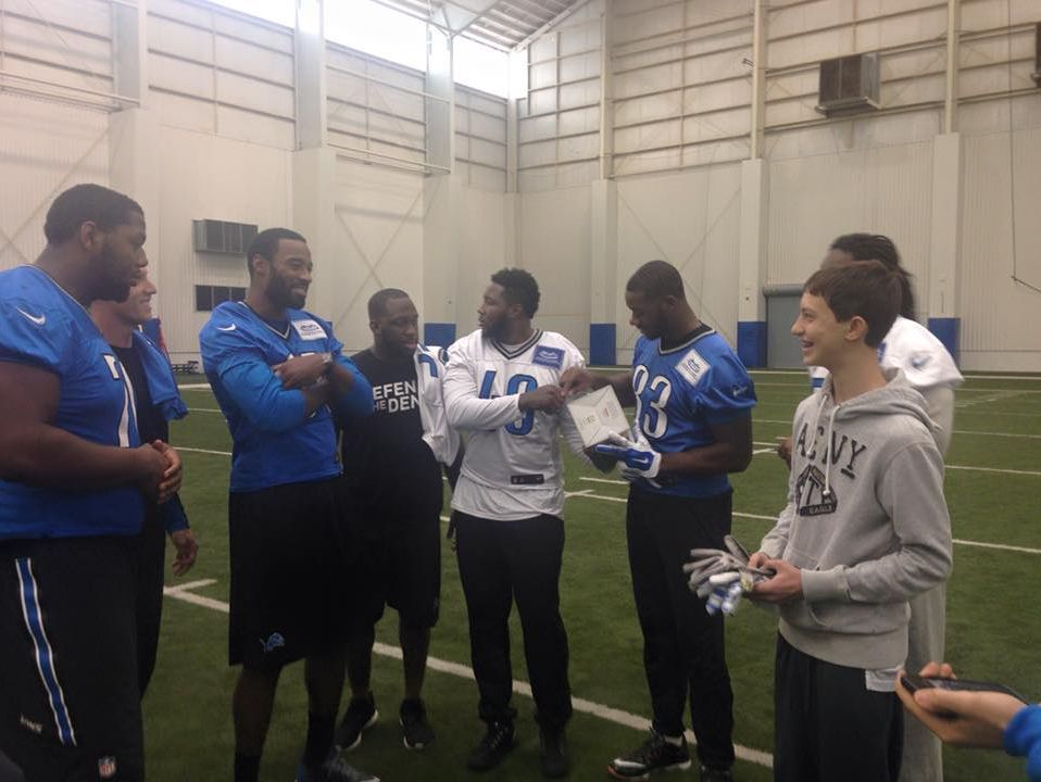 Former Lions receiver Calvin Johnson, left with arms crossed, gave Sam Kell his gloves at practice in December 2015.