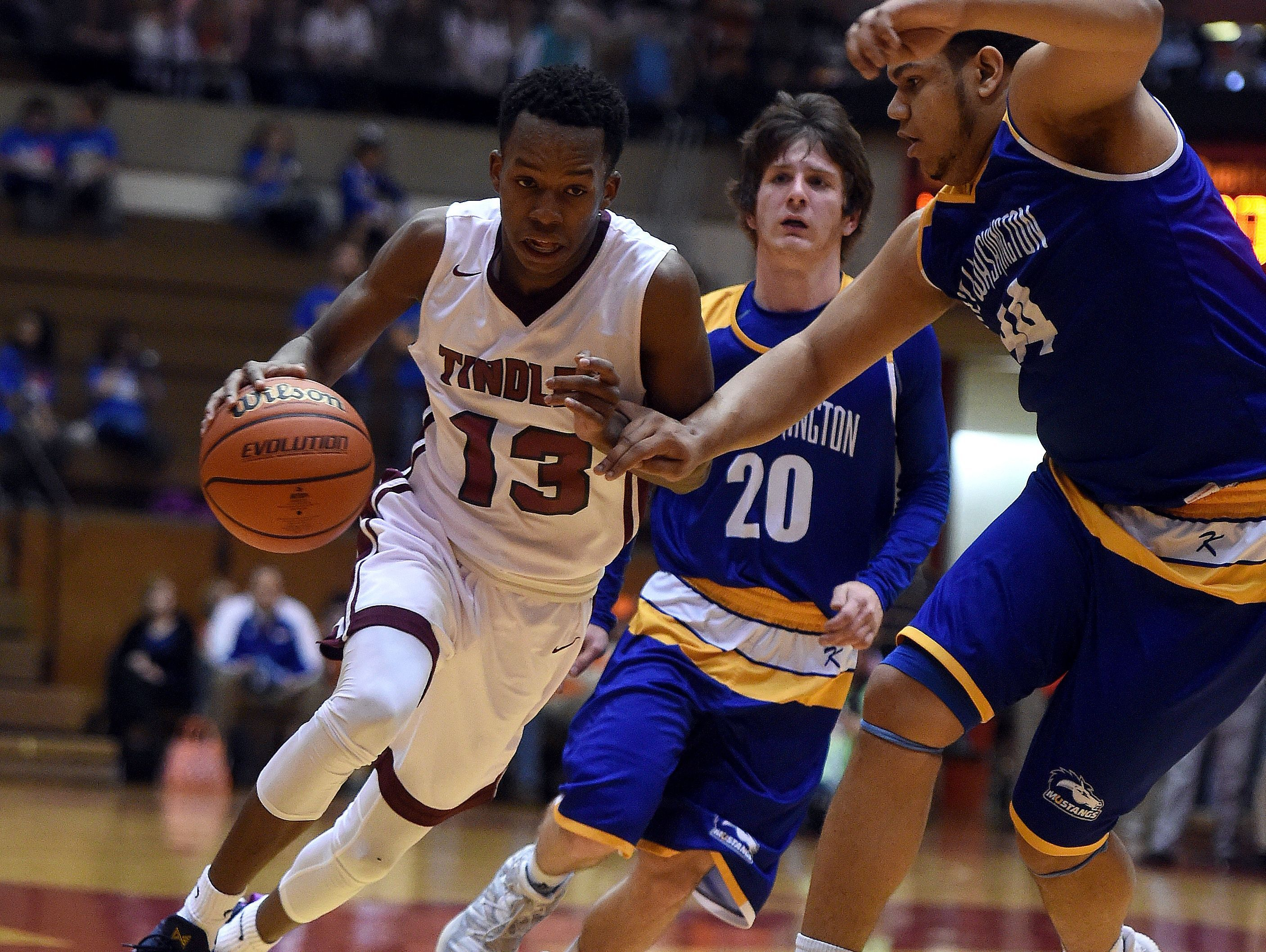 Tindley's Eric Hunter moves the ball against New Washington's Brandon Horton and Stevie Mack Saturday, March 18, 2017 during the Class A basketball semi-state championship in the Tiernan Center at Richmond.