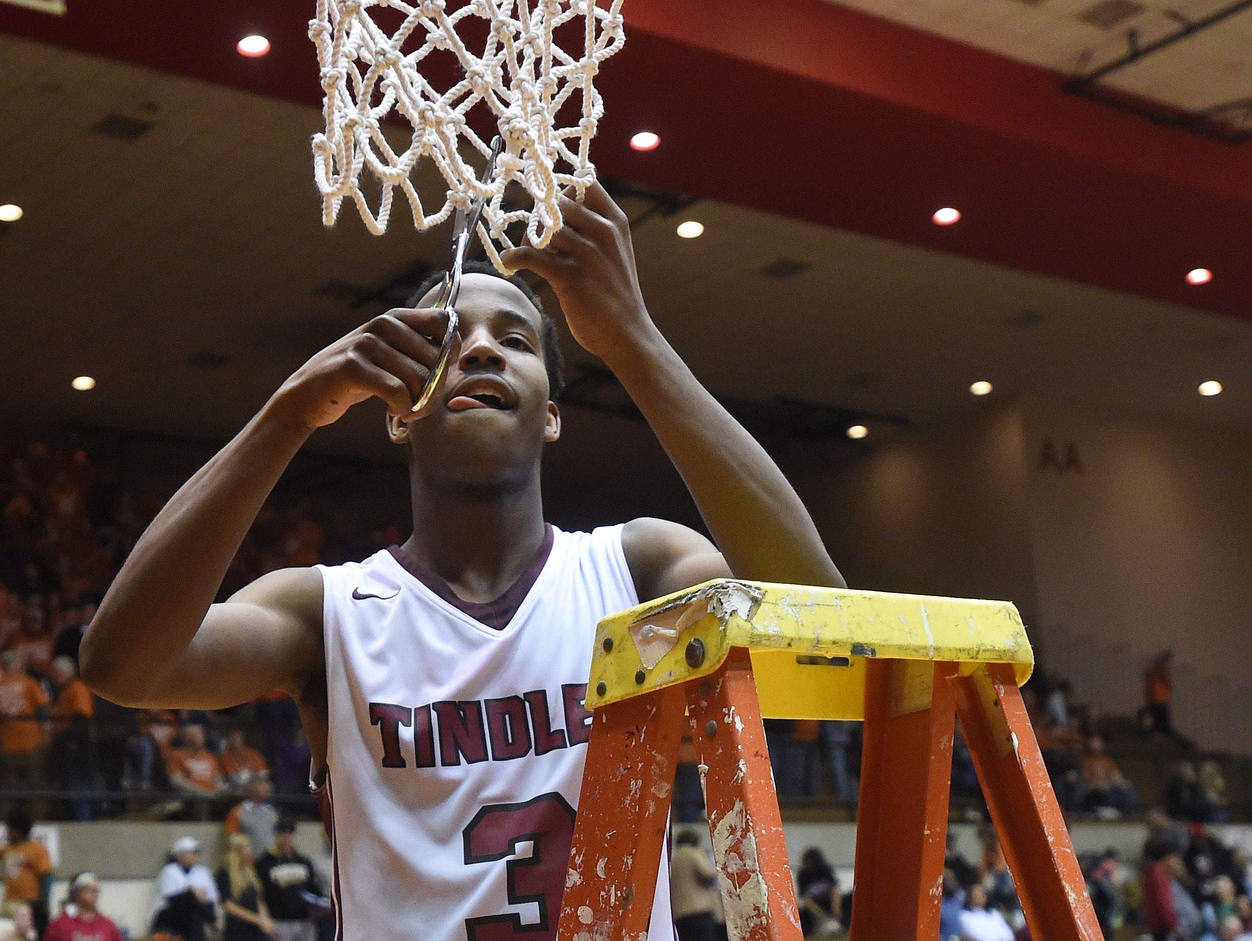 Tindley's Hunter White cuts down part of the net after beating New Washington Saturday, March 18, 2017 for the Class A basketball semi-state championship in the Tiernan Center at Richmond.