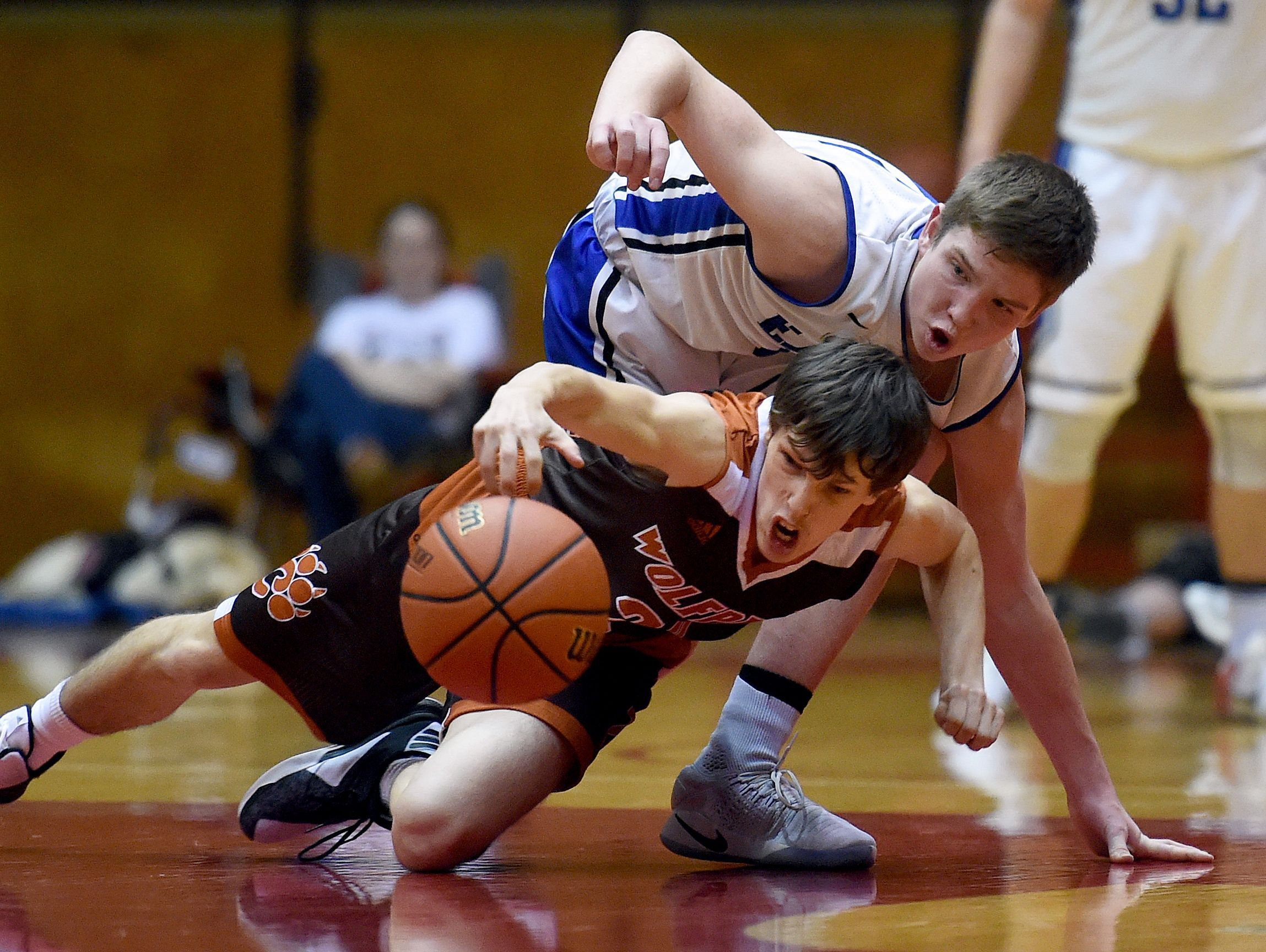 Crawford County's Noah Sturgeon and Heritage Christian's Andrew Williams dive for the ball Saturday, March 18, 2017 during the Class 2A basketball semi-state championship in the Tiernan Center at Richmond.