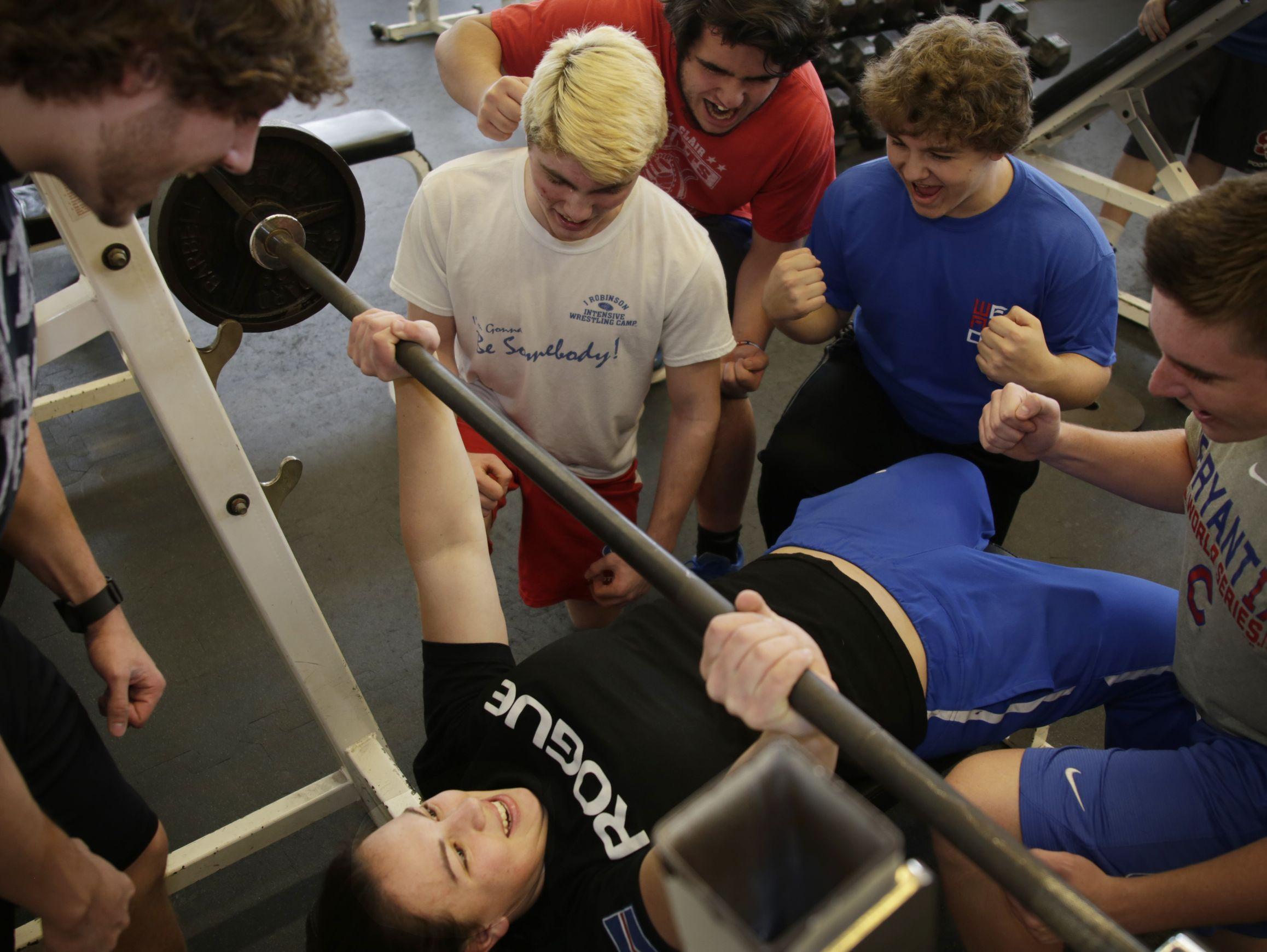16-year-old Molly Likins of St. Clair, who has undergone a Cochlear implant, just set the state powerlifting bench press record and gets some encouragement as she lifts during a photo shoot by some members of the St. Clair Saints football team at St. Clair High School Tuesday Mar. 14, 2017.