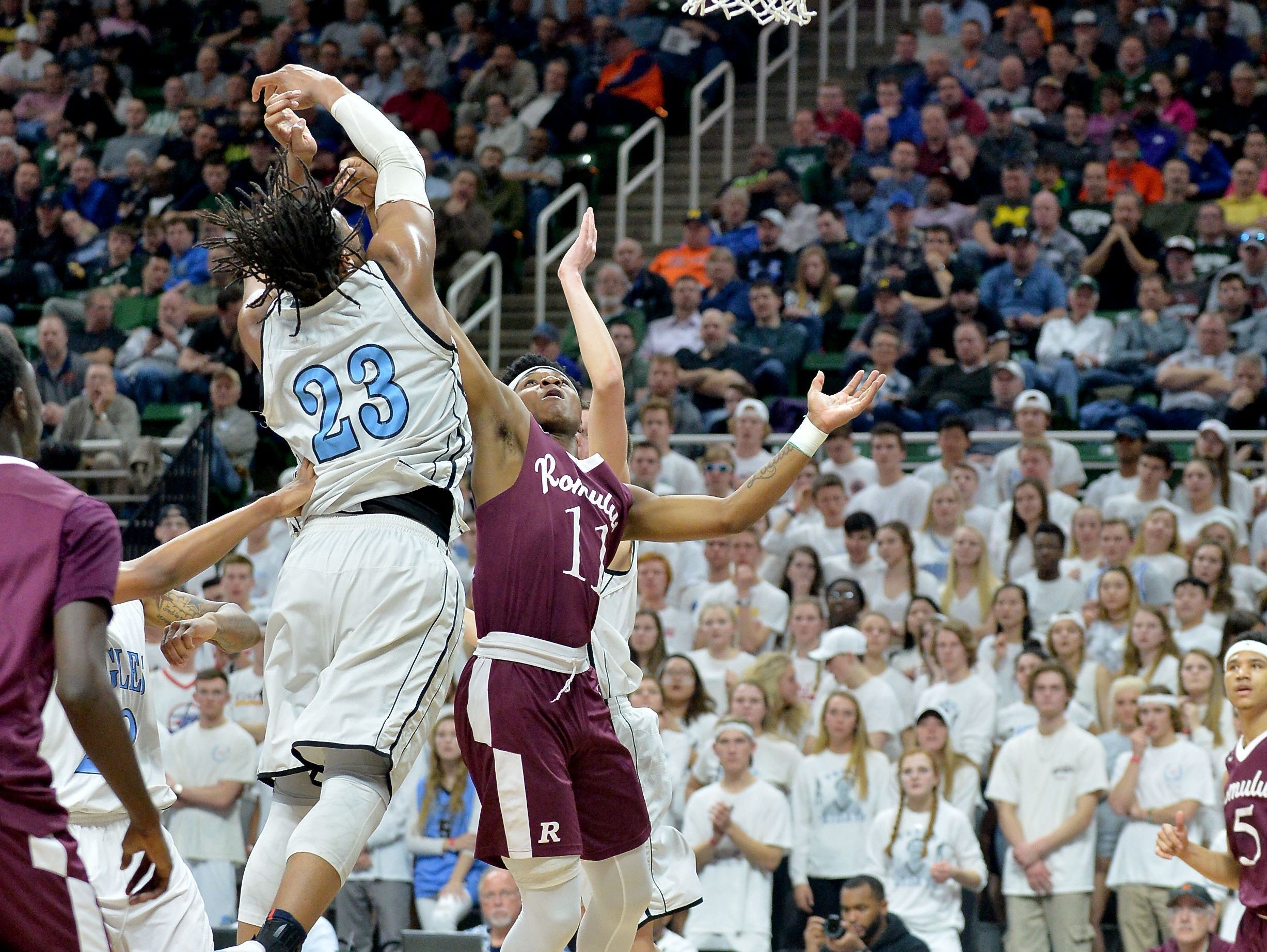 Grand Rapids Christian star forward and Michigan State signee Xavier Tillman (23) battles Romulus junior Braedon Morgan for a loose ball in a Class A semifinal on Friday, March 24, 2017 at the Breslin Center.
