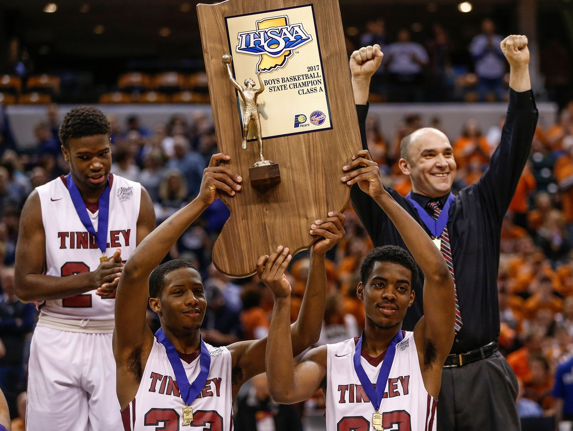 The Tindley Tigers hoist the IHSAA Class A state championship trophy after their 51-49 win over the Lafayette Central Catholic Knights at Bankers Life Fieldhouse in Indianapolis on Saturday, March 25, 2017.
