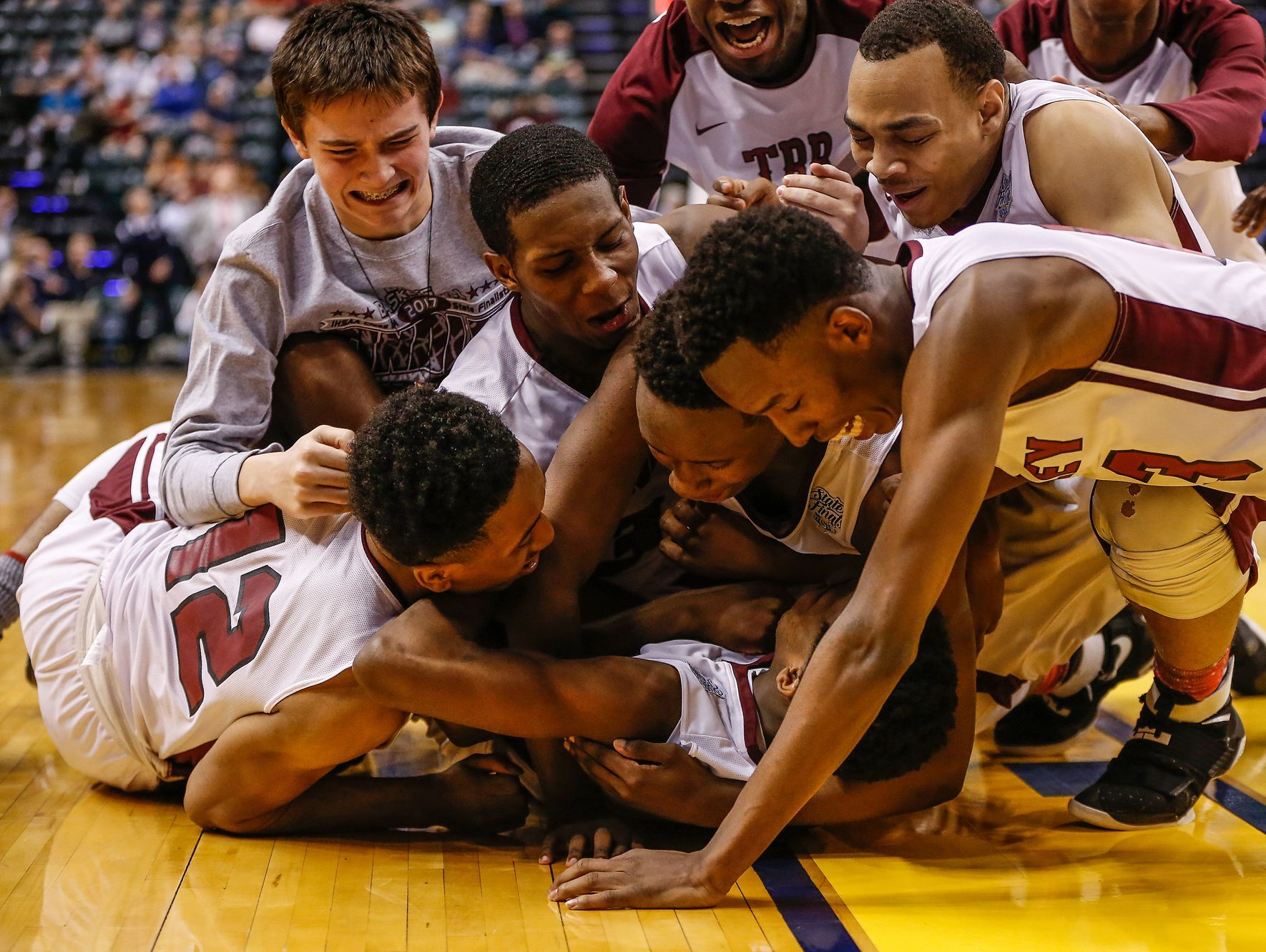 The Tindley Tigers bench clears as they tackle the Tigers' Hunter White (3) after he connected on a short jumper that put the Tigers up 51-49 over the Lafayette Central Catholic Knights as the time ticked off the clock in the fourth quarter during the IHSAA Class A state championship game at Bankers Life Fieldhouse in Indianapolis on Saturday, March 25, 2017.