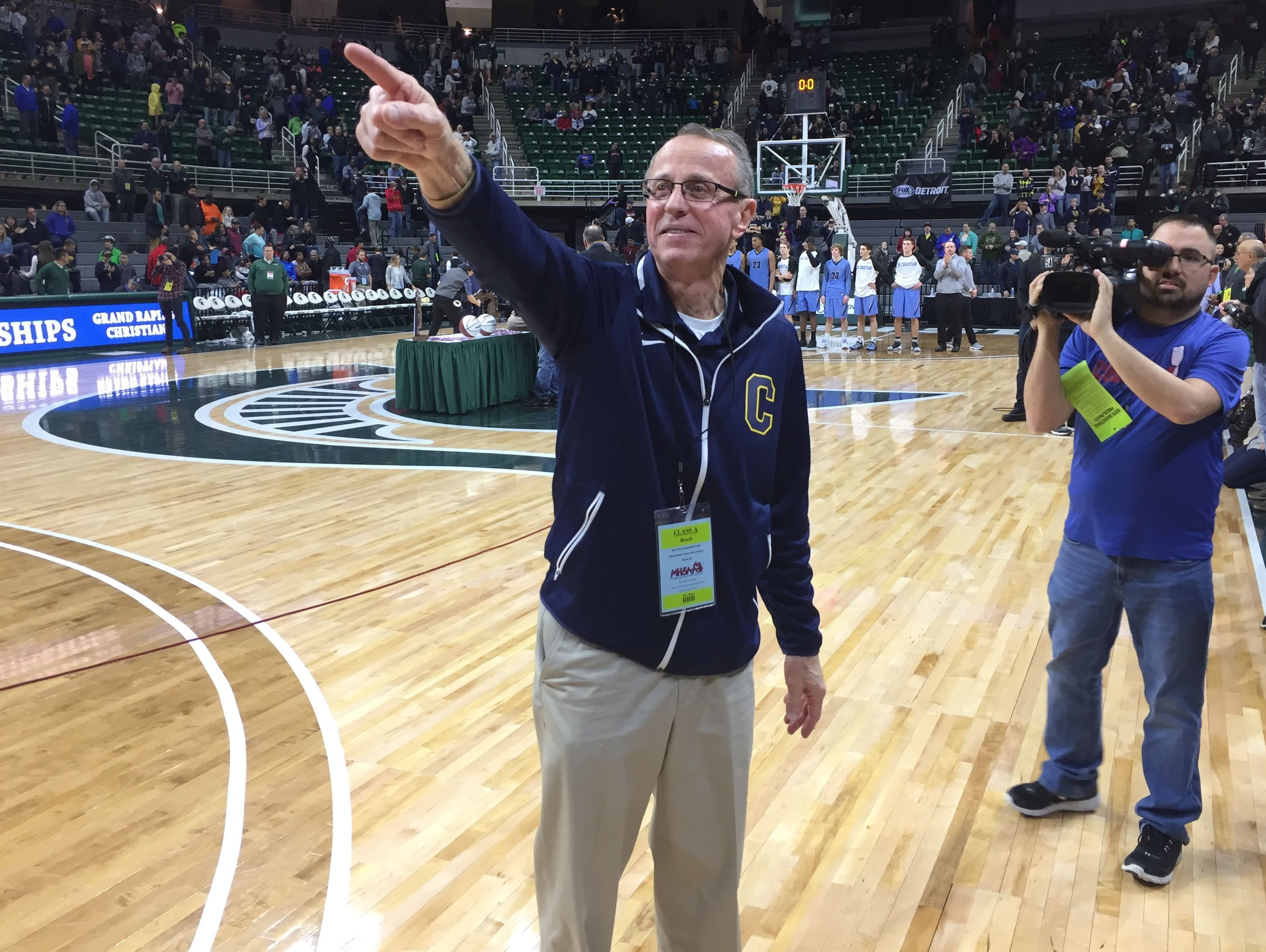 Clarkston coach Dan Fife points to the crowd after his team's 75-69 win over Grand Rapids Christian in the Class A final at the Breslin Center on Saturday, March 25, 2017.