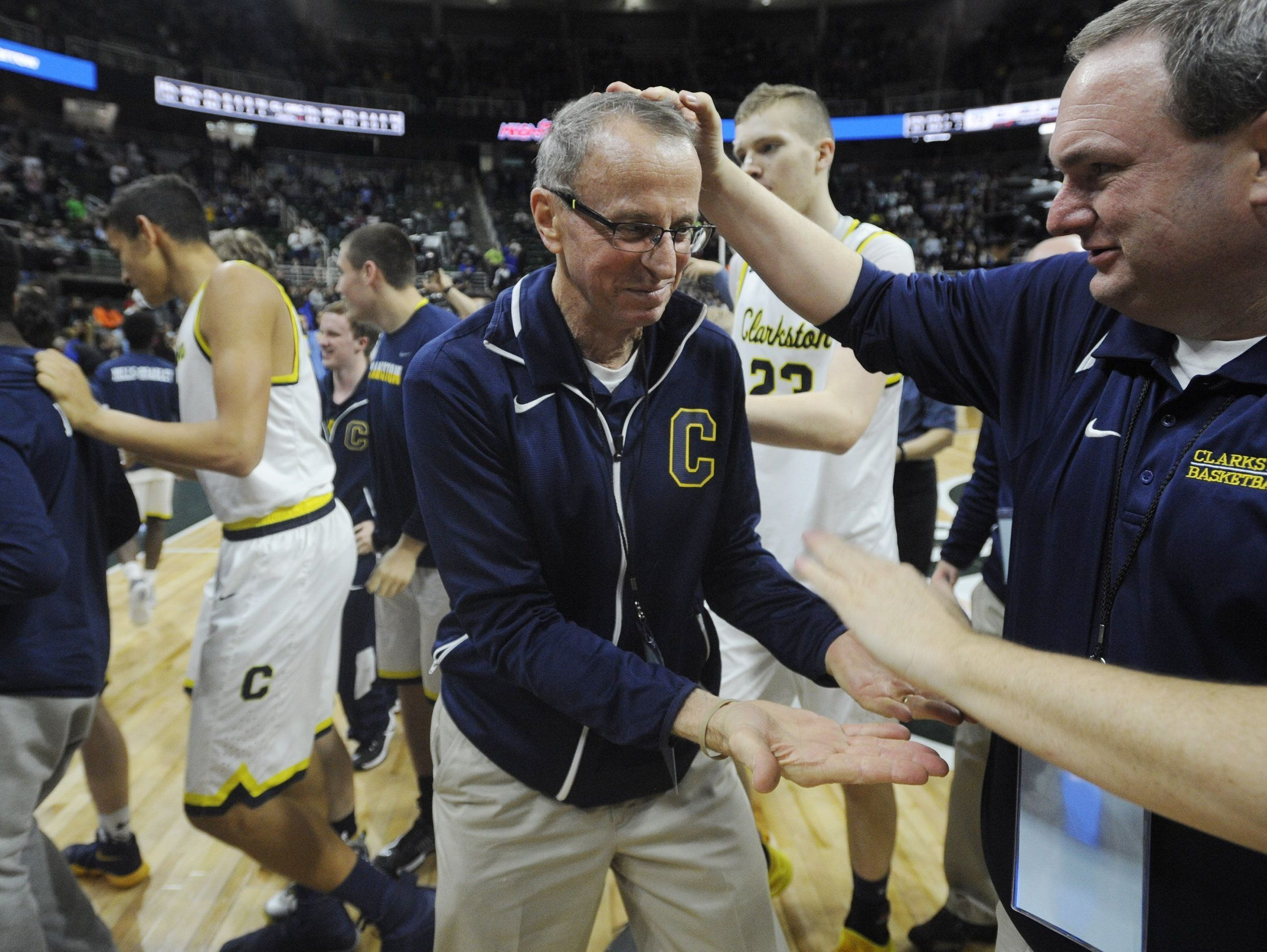 Clarkston head coach Dan Fife, left, accepts congratulations after defeating Grand Rapids Christian, 75-69, in the MHSAA Class A boys basketball final at the Breslin Center on Saturday, March 25, 2017.