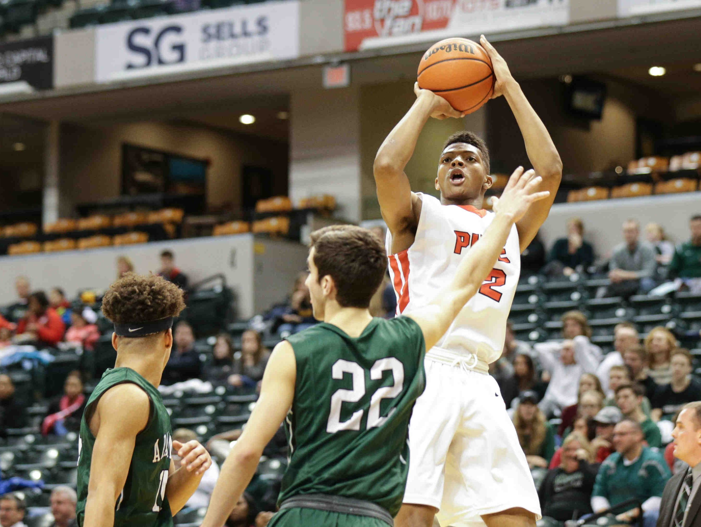"""Pike High School's Isiah James (42) hits a 2 point shot over Pendleton Height's Eston Stull (22) and Eli Pancol (14), during """"The Really Big Basketball Show, 2017"""", held at Bankers Life Fieldhouse, Jan 28, 2017. Pendleton Heights vs. Pike."""