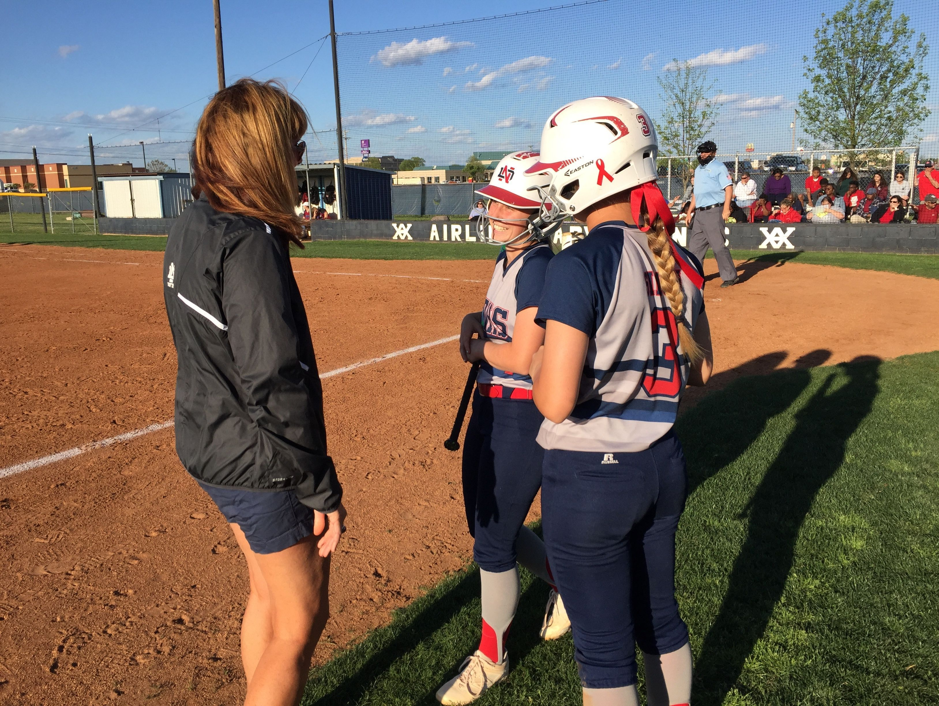 North DeSoto coach Lori McFerren discuses a play with Amber Giddens and Bayli Simon during Thursday's game with Minden at the Airline field.