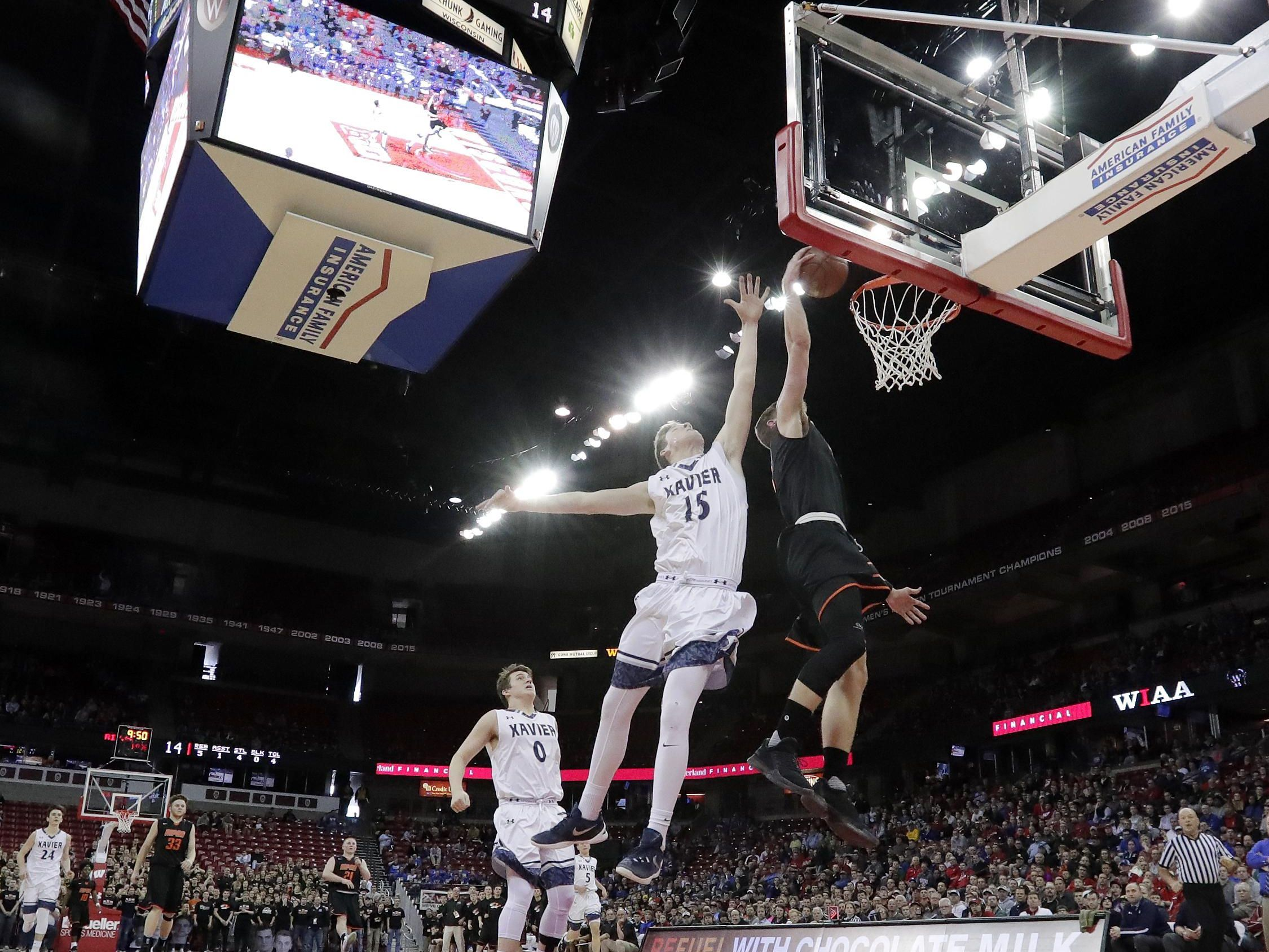 Ripon's Bennett Vander Plas (1) dunks over Xavier's Nate DeYoung (15) in a WIAA Division 3 semifinal at the boys basketball state tournament at the Kohl Center on Thursday.