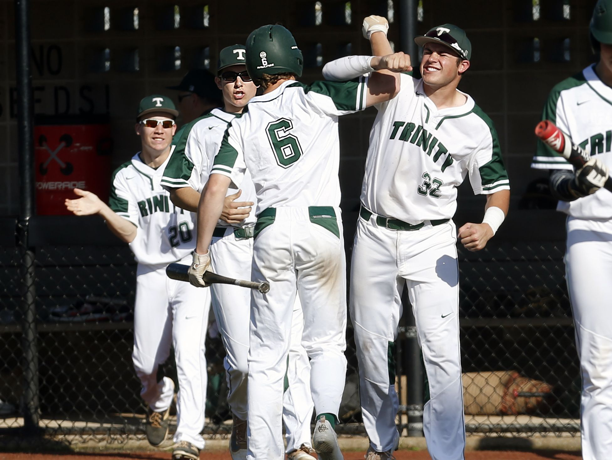 Trinity's Matt Higgins celebrates with his team after scoring a run against St. X. May 13, 2016