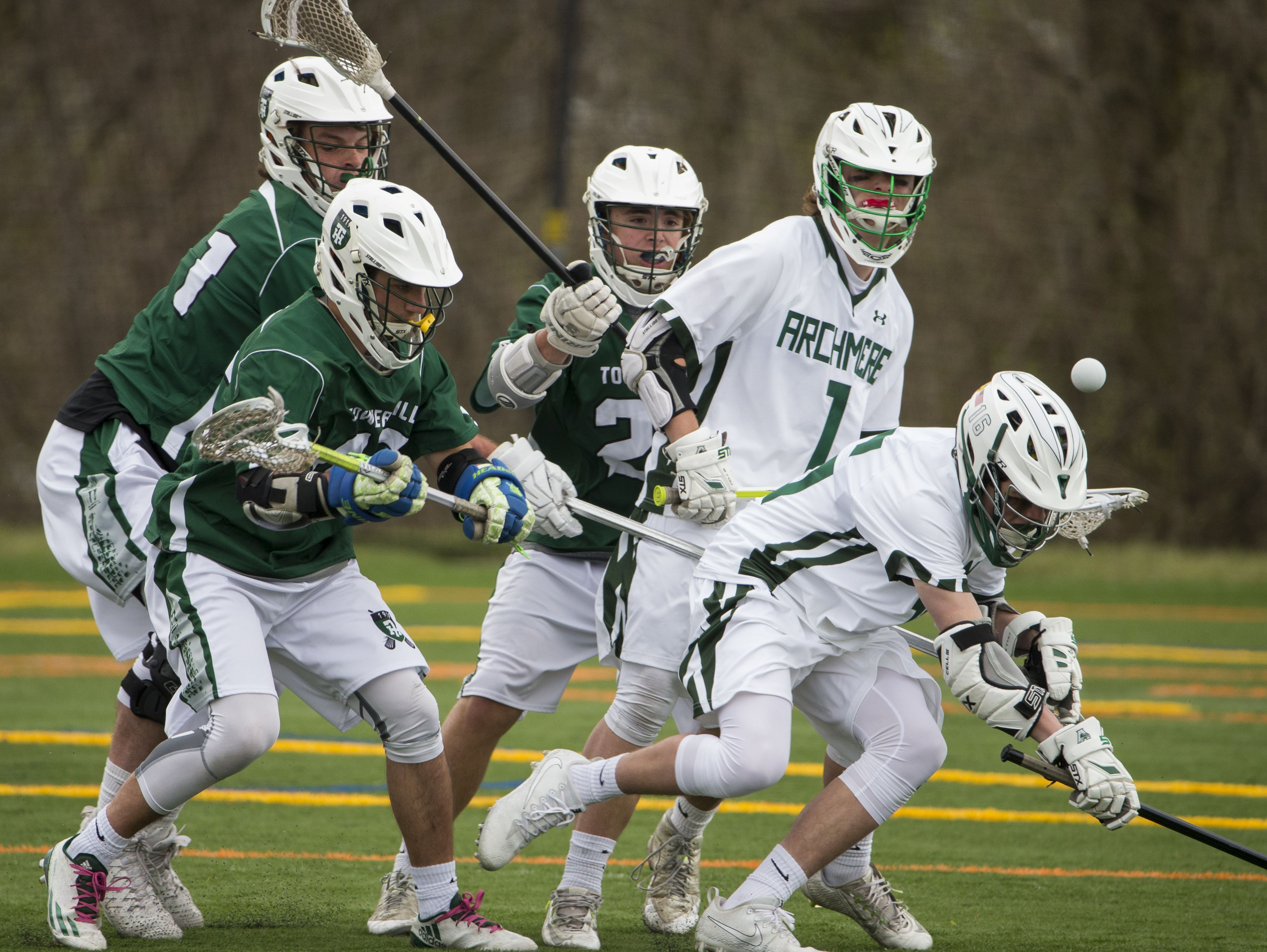 Archmere's Nolan Collins (right) runs into traffic in front of the Tower net in the second half of Archmere's 12-7 win Saturday.