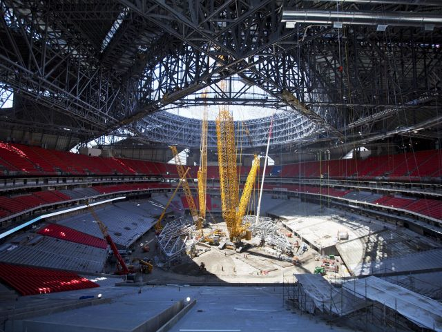 Cranes poke through the retractible roof under construction inside Mercedes-Benz Stadium, the new stadium for the Atlanta Falcons NFL football team in Atlanta, Tuesday, April 25, 2017. The challenge with the retractable roof has been installing the eight triangular steel petals that would enable it to retract and open like a camera lens. Water-tight seals are being installed on the petals, then it'll take eight weeks to place fluorine-based plastic on them, a spokeswoman said. In early June, workers will bring the petals together for proper alignment with the help of two gigantic crawler-cranes. (AP Photo/David Goldman)