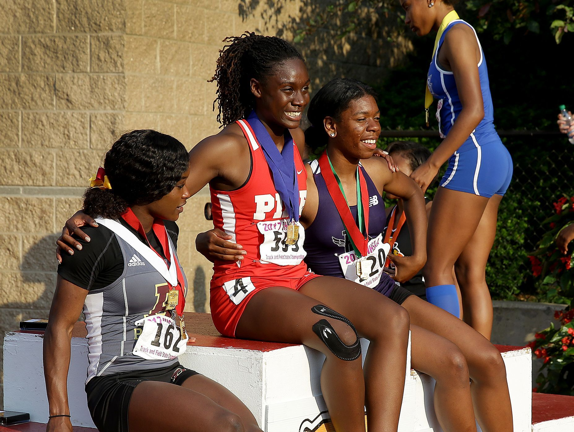 Pike's Lynna Irby (599) hugs her competitors and get photos taken following the Girls 200 Meter dash during the girls IHSAA State Finals.